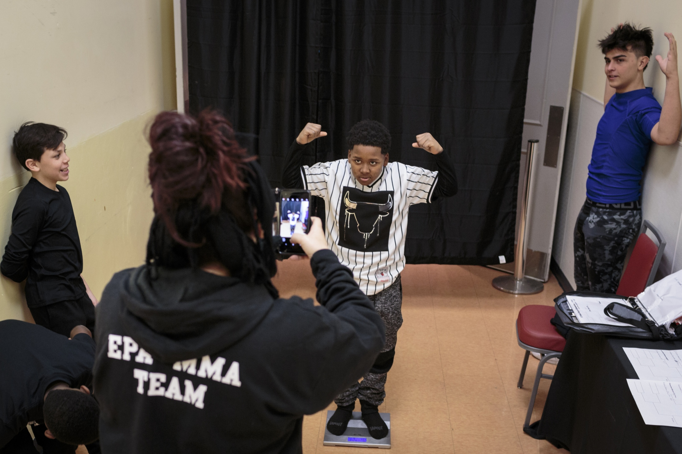 Coach Audra Saldana takes photos of Brian Owens, 11, middle, posing on a scale after his weigh in before the U.S. Open Youth National at Isle of Capri in Boonville, Missouri.