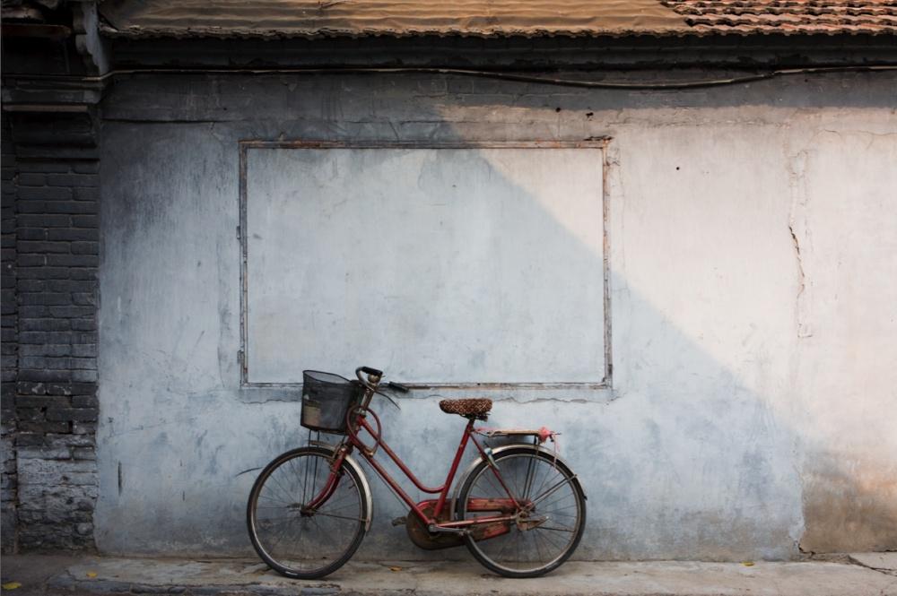 Bicicleta reclinada sobre una vivienda. Es el medio de transporte de al menos tres millones de habitantes, las cuales están siendo reemplazadas gradualmente por las motocicletas / Bicycle reclined in a traditional housing. It is the means of transportation for at least three million inhabitants of Beijing, which are being substituted by motorcycles exponentially. Beijing / Pekín