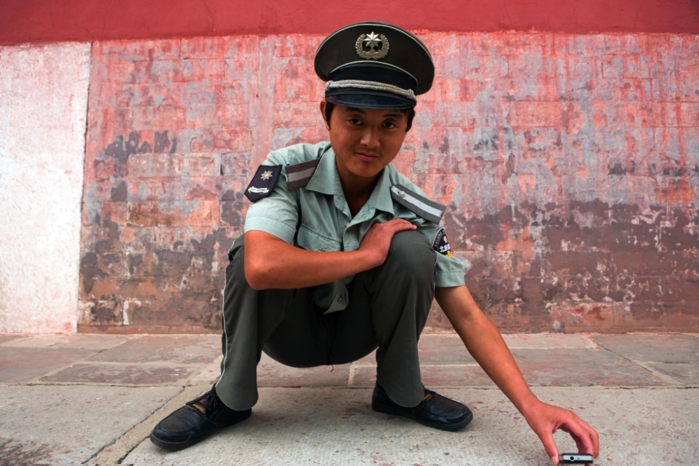 Guardia de las Tumbas Ming compartiendo música de rap local desde su teléfono celular / Guard of the Ming Tumbs sharing a chinese rap song from his cel phone Fachada de una tienda. Beijing / Pekín