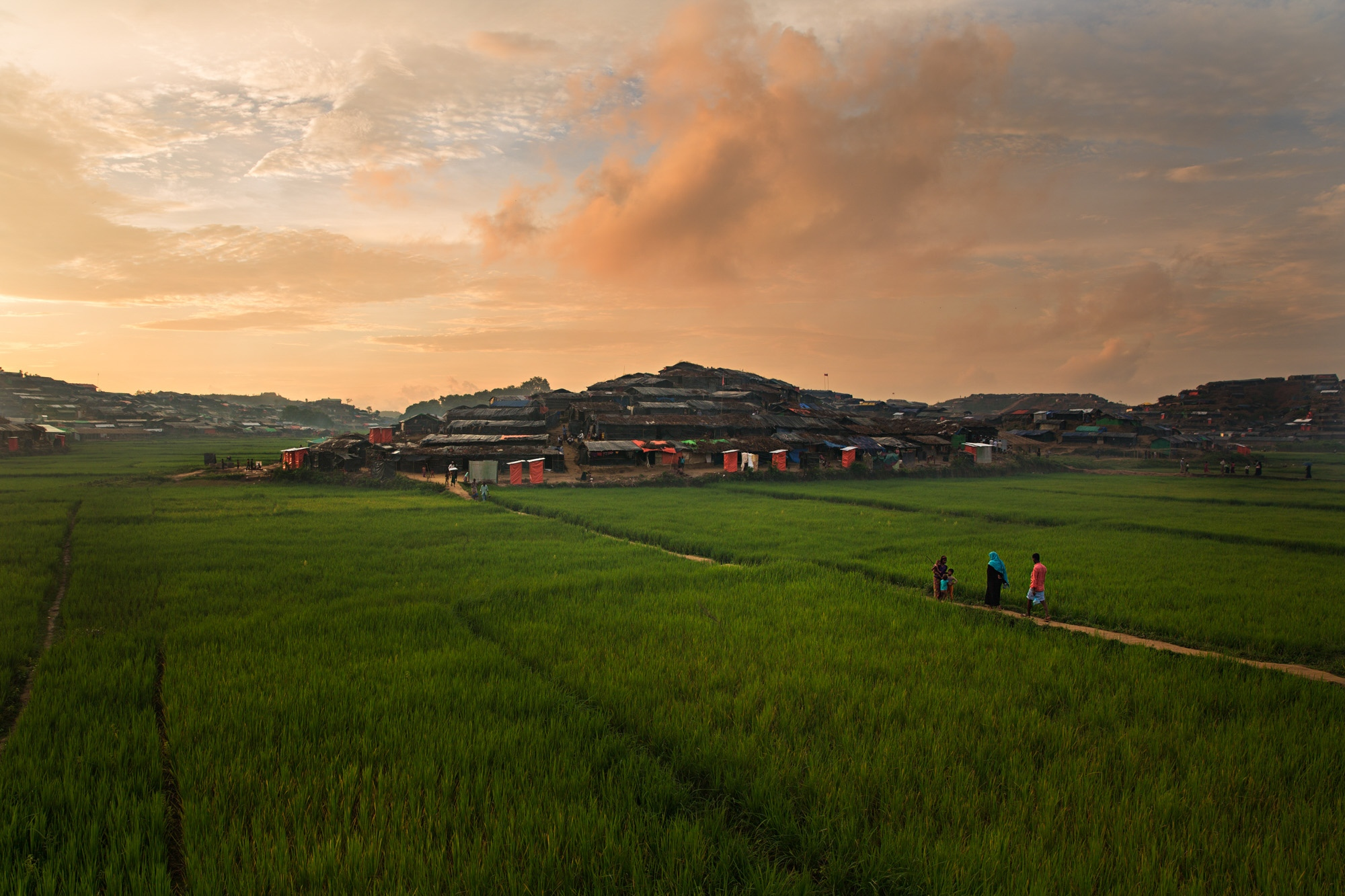 Rohingya refugees walk through Bagoha camp at sunset. Though beautiful, the reality of the camps is harsh, cramped and unforgiving. Despite the violence that they fled, many Rohingya wished to someday return to their homes.
