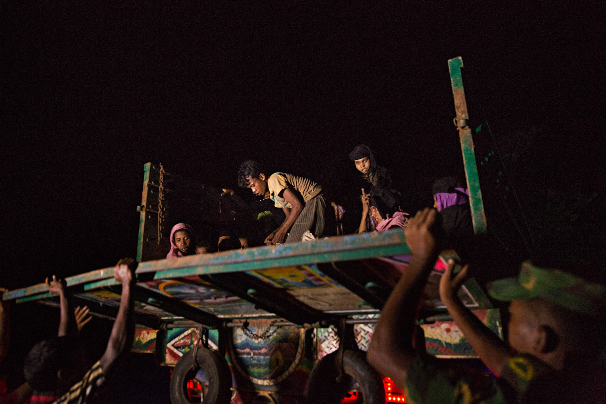 Rohingya refugees are loaded into a truck under the cover of darkness, after crossing the Naf River by boat from Myanmar to Bangladesh. The truck drives them to the camps where they will be left by the side of the road until they can be assigned a space to set up a tent.