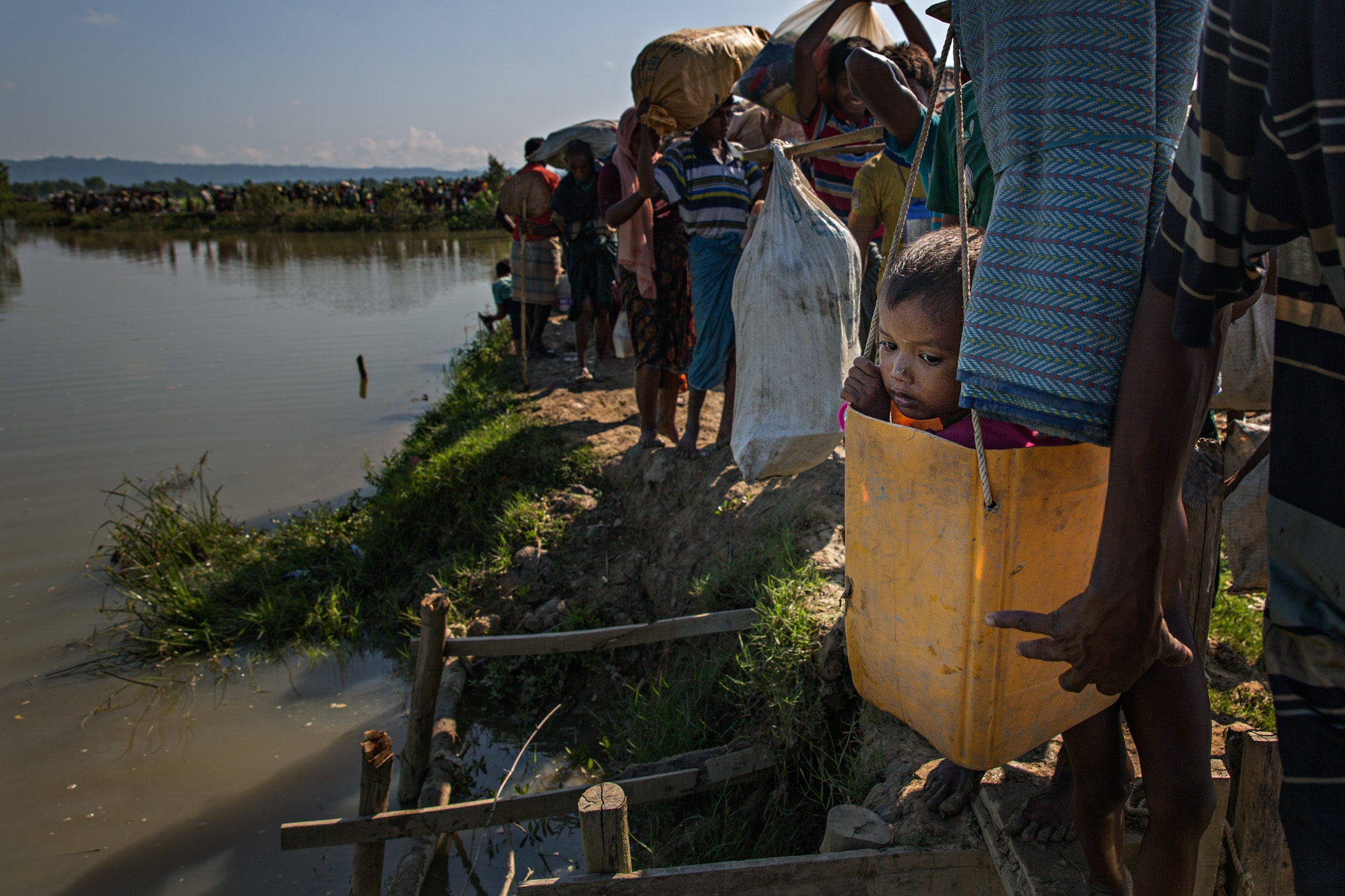 A Rohingya child is carried in a bucket along a muddy path in a rice paddy field immediately after crossing the Naf River, from Myanmar into Bangladesh. The journey took many families a week or more and the very young and very old often had to be carried in whatever way possible.