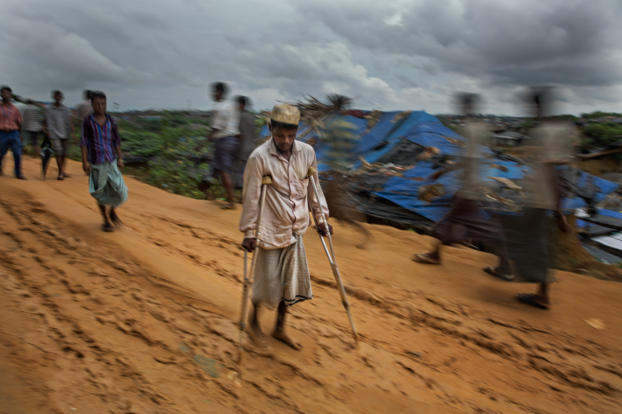 A Rohingya man slowly makes his way through Kutapalong camp. Heavy rains, foot traffic and hundreds of passing vehicles turned the newly formed roads into a slippery, dangerous quagmire.