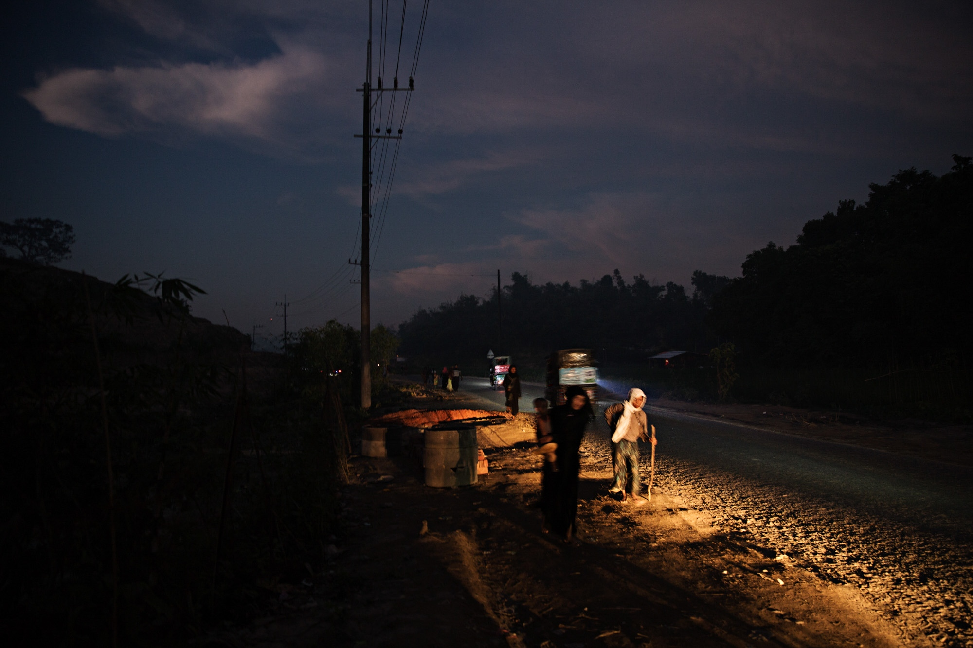 Rohingya refugees make their way along the road next to Balukali camp. The road through the camps experienced heavy traffic and refugees were regularly hit, some fatally so.