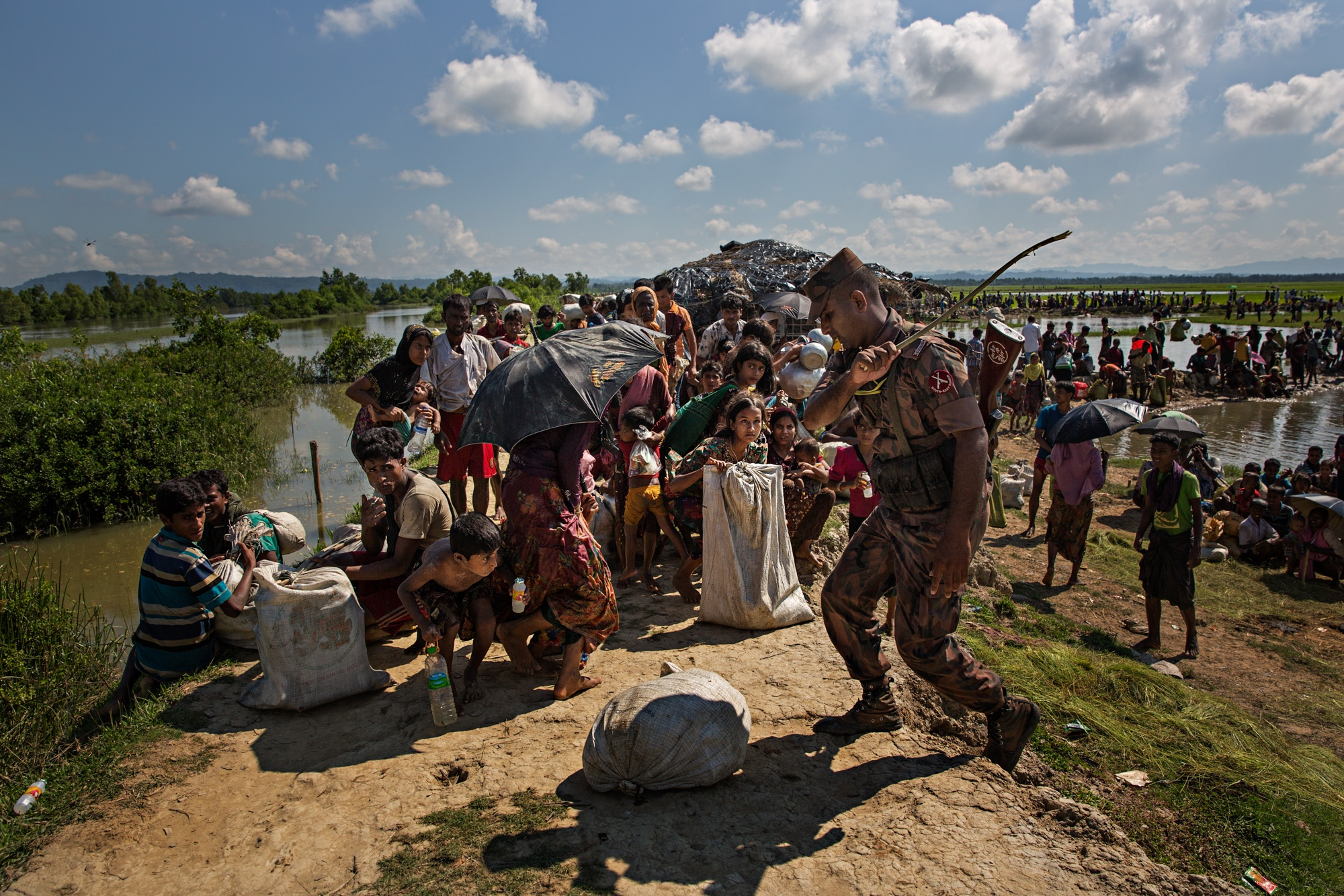 Rohingya refugees are kept in line with a stick wielded by a Border Guard Bangladesh (BGB) member after crossing the Naf River from Myanmar into Bangladesh. Many had been walking for weeks and were suffering from malnutrition and dehydration. Temperatures reach well over 100 degrees Farenheit.