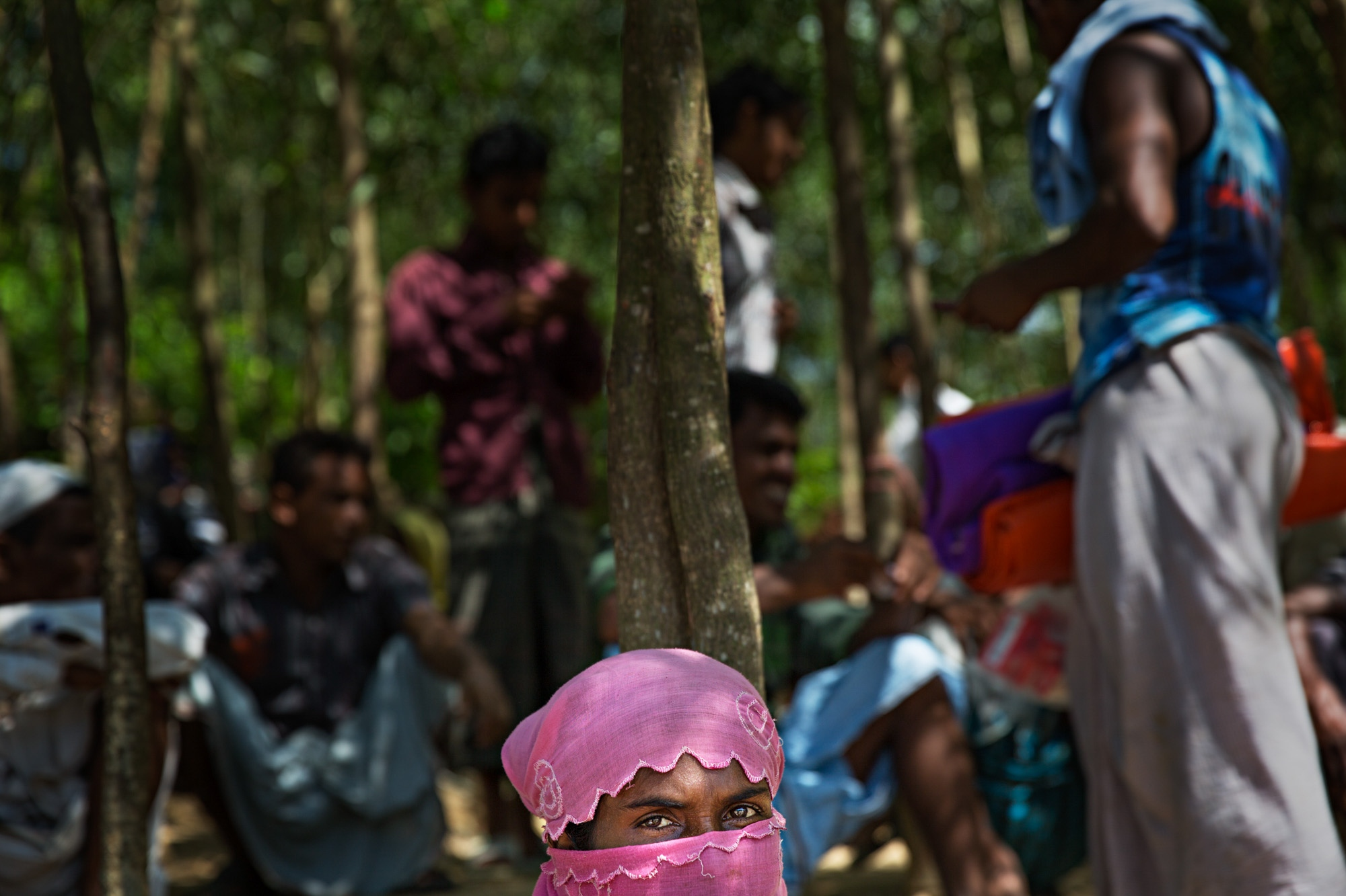 A Rohingya woman awaits camp assignment in the shade on the edge of the road on October. New arrivals from Myanmar waited for camp assignment by the roadside in whatever shade they could find for an undesignated amount of time.