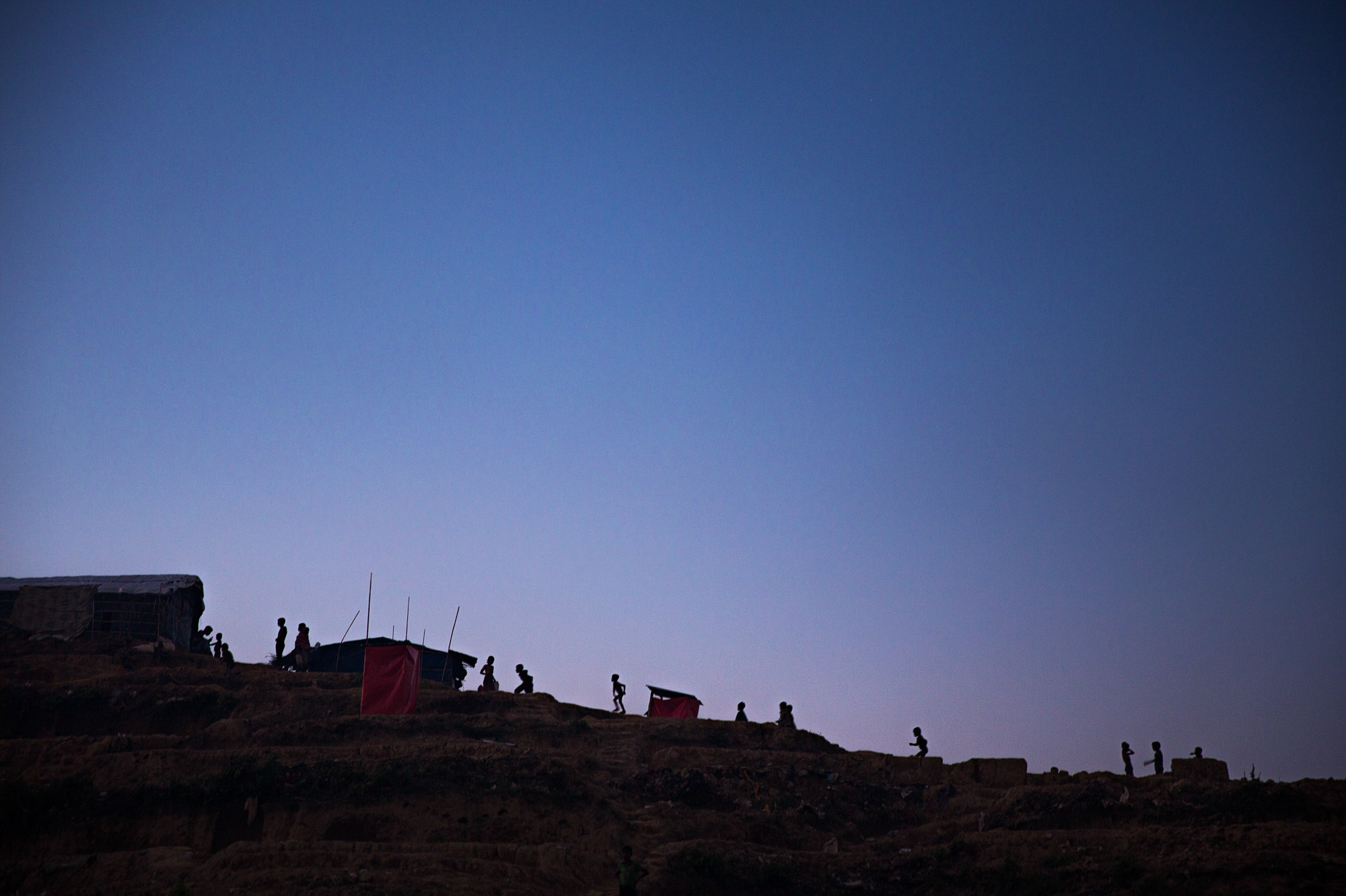 Silhouettes of children playing line the ridge of Balukali camp. The camps often became most active a night as the unrelenting heat of the day finally abated.