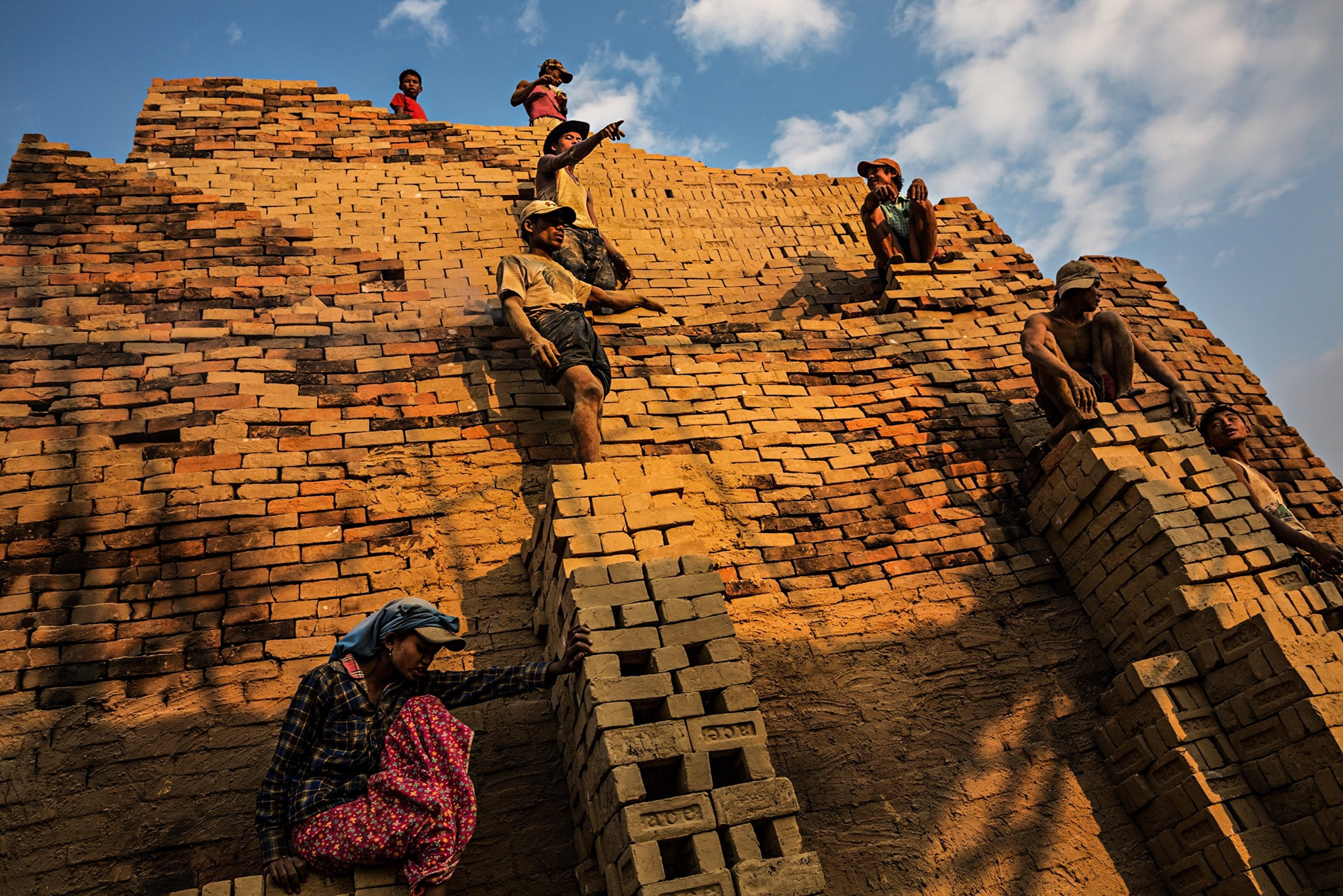 Brick factory workers stand on the side of a kiln, passing bricks to the top. The kilns can reach heights of twenty-five feet and those who opt to work higher up can earn a very small extra sum.