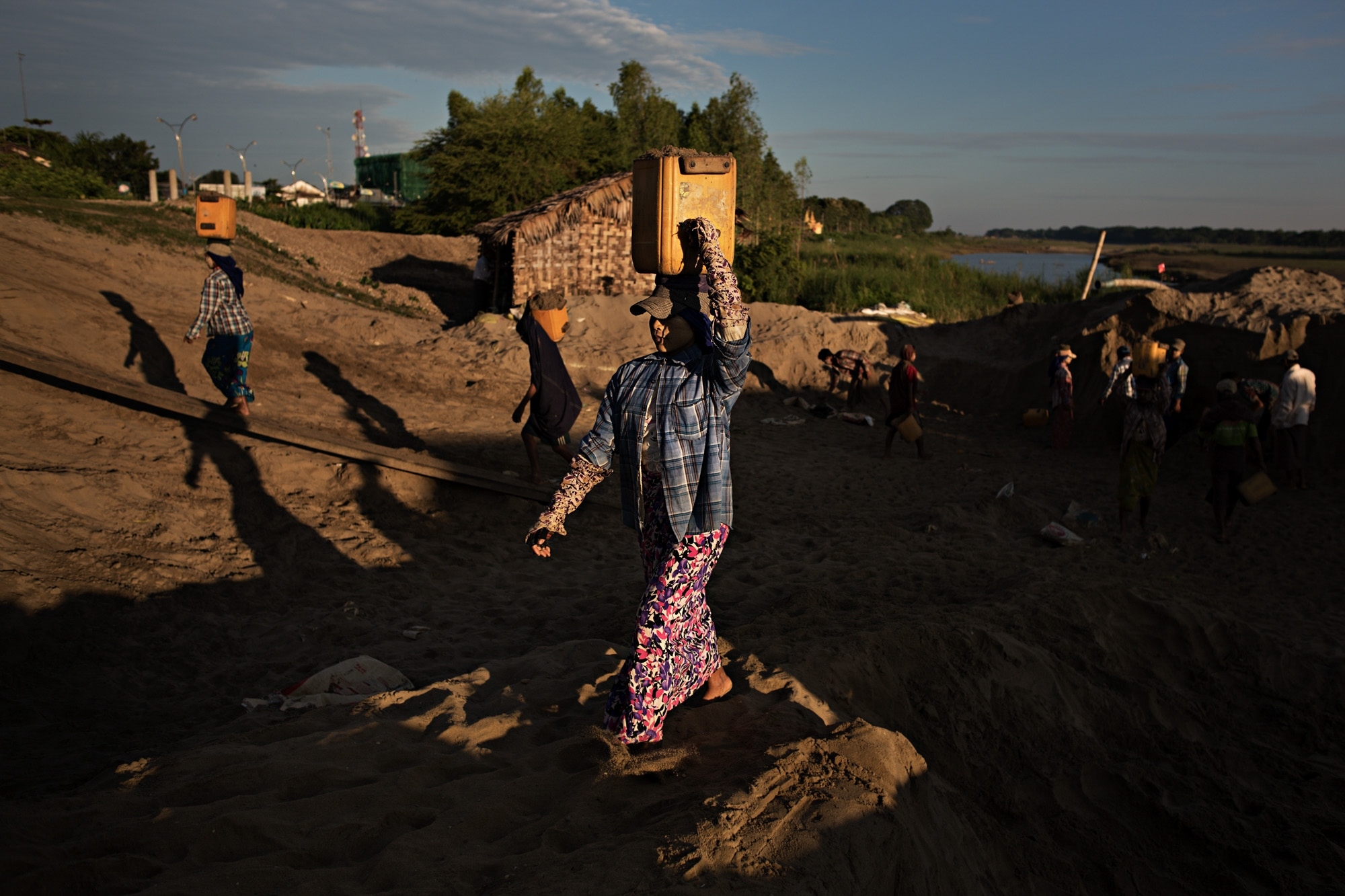 A woman carries sand to a truck. Sand mining is a huge industry and most of it is unregulated, leading to a lot of environmental damage.