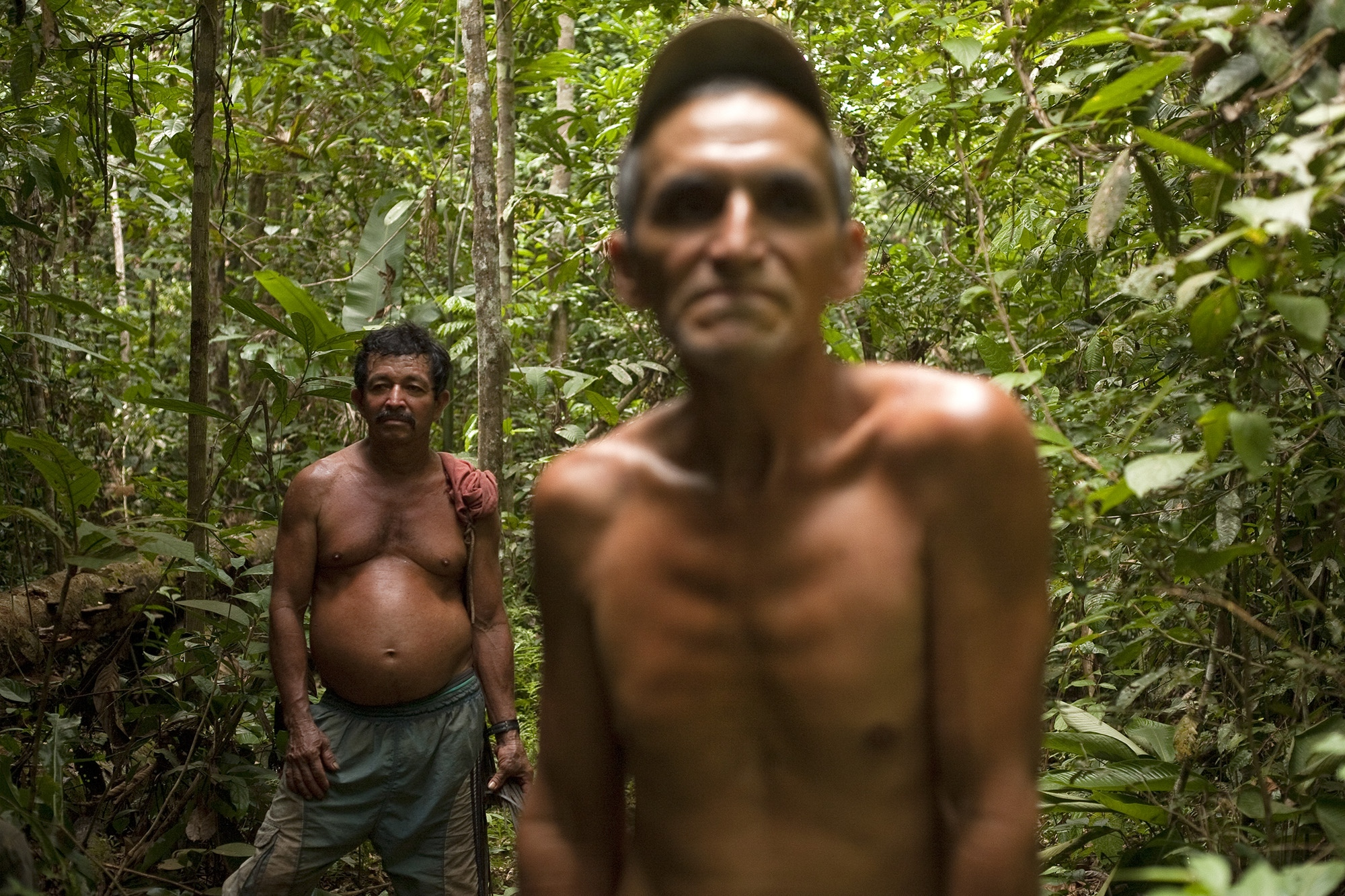 "Francisco Manuel García (r) and Otto Felix Forero (l), pause in the jungles of the department of Guaviare, after finishing their day of work as ""raspachines"" or coca leaf collectors, which they have been doing for more than 20 years."