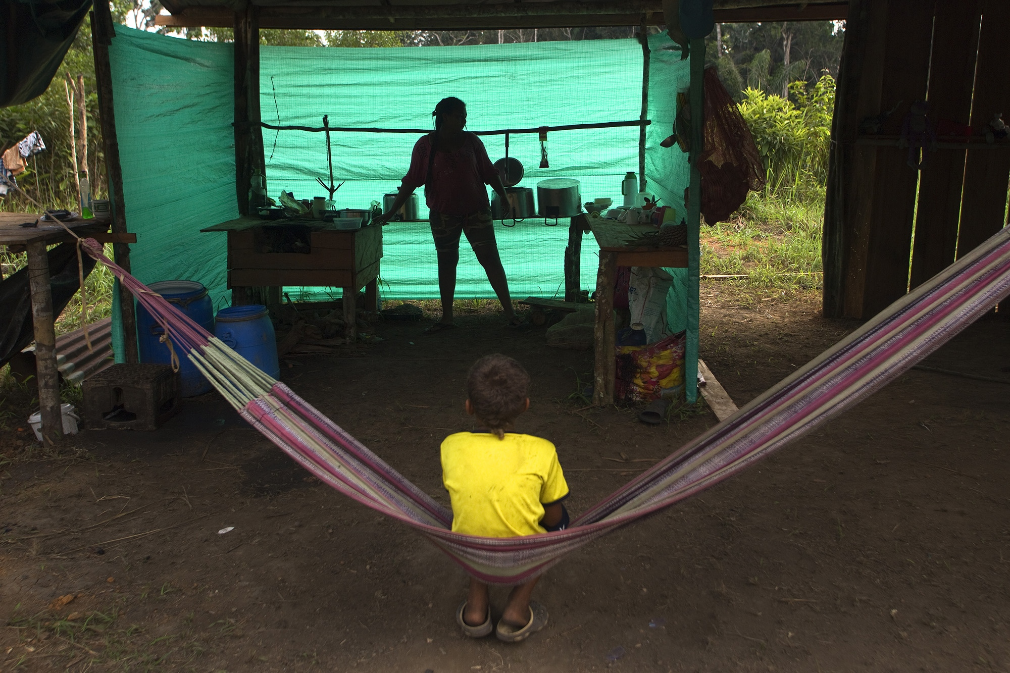 Aida Rodriguez Sanchez and his son Estiven on his farm in the La Paz, Guaviare. Aida survives picking coca leaves, as the great majority of inhabitants of this area of Colombia.