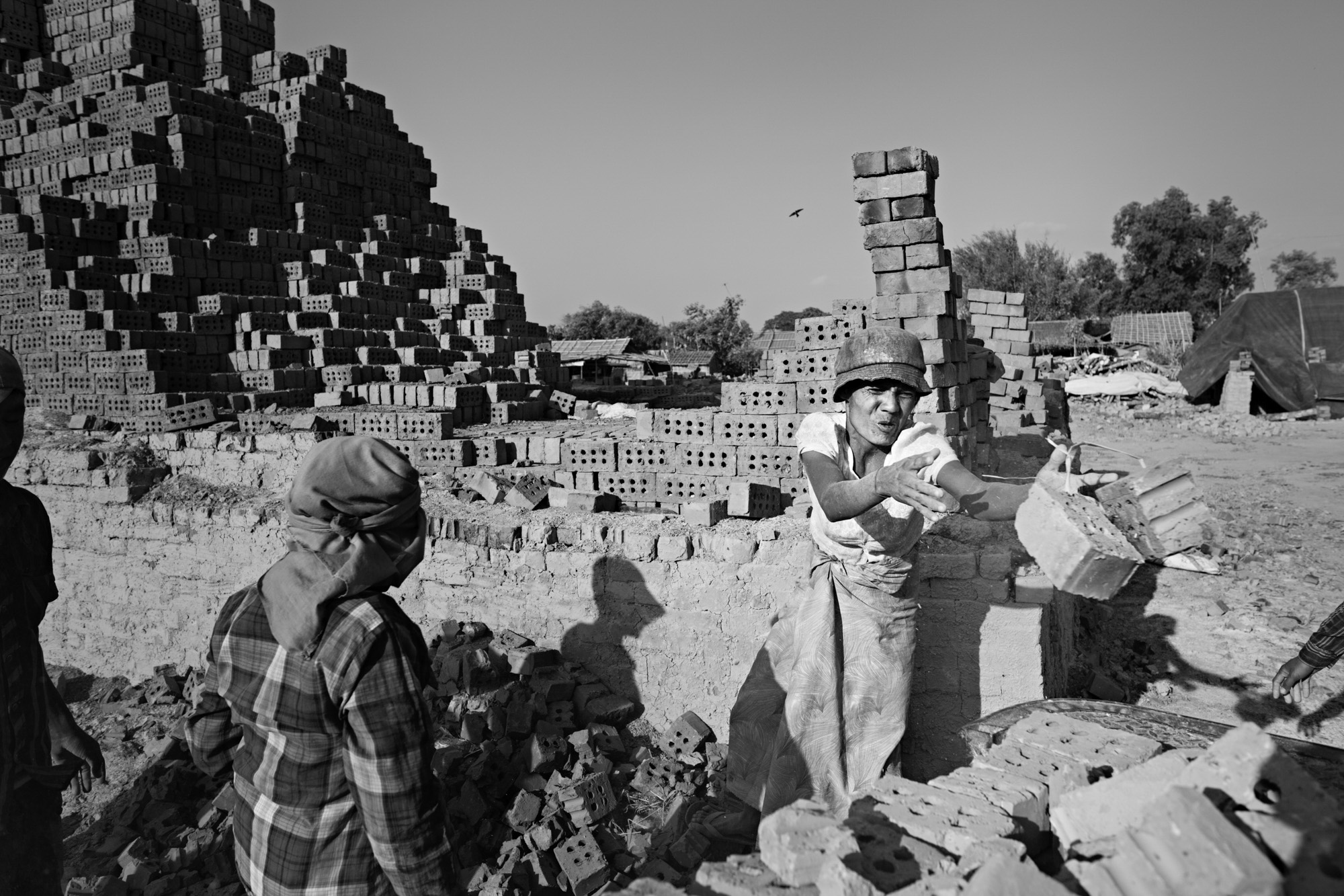 Than Nwe tosses bricks, destroyed by the kiln fires, into a rubish cart. When they are not making new bricks, Naing Lin, Than Nwe and Naing Lin Oo work odd jobs to earn extra money.