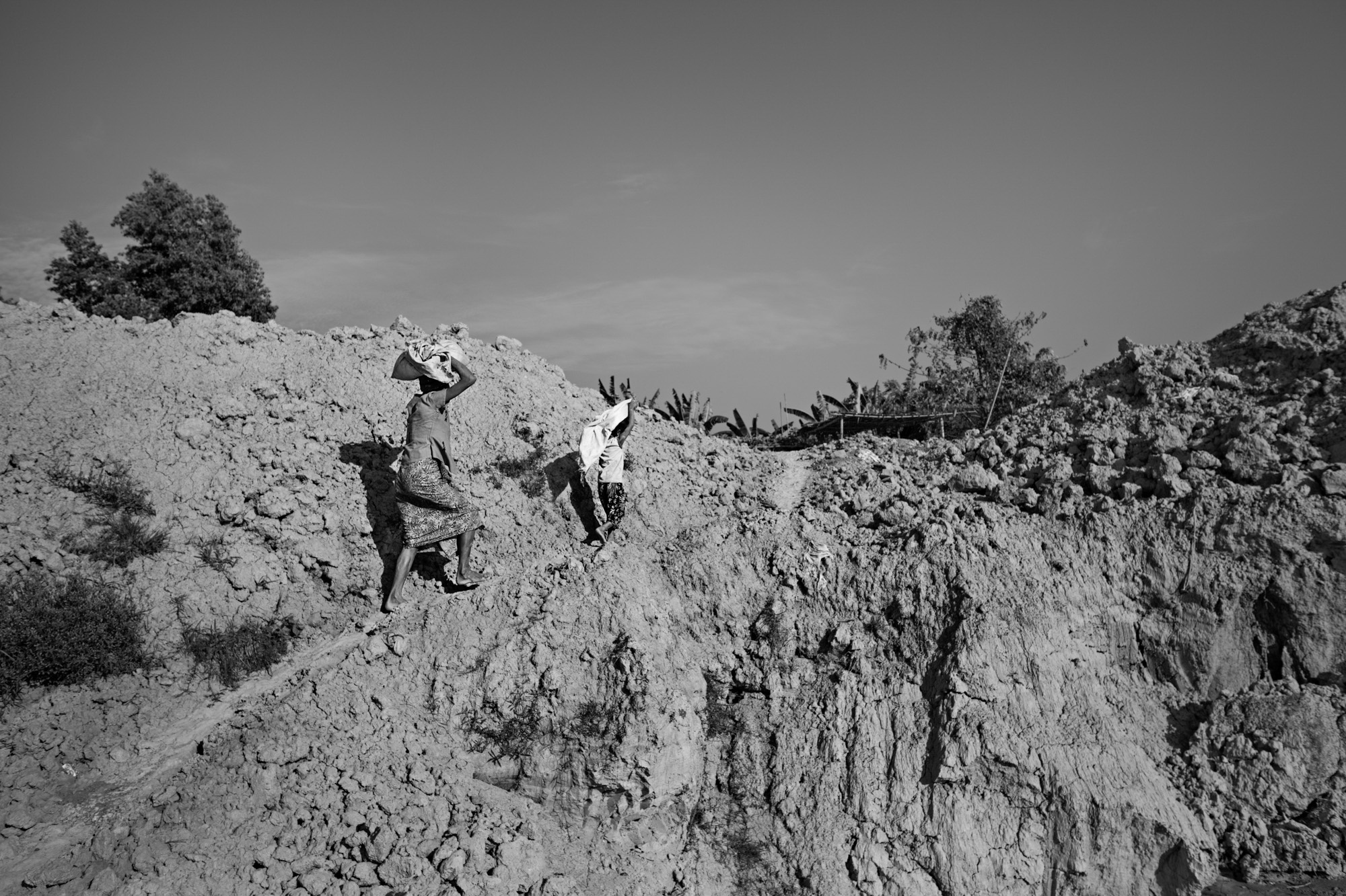 Than Nwe and Saung Ning Wai carry sacks of clay up to their brick making station.