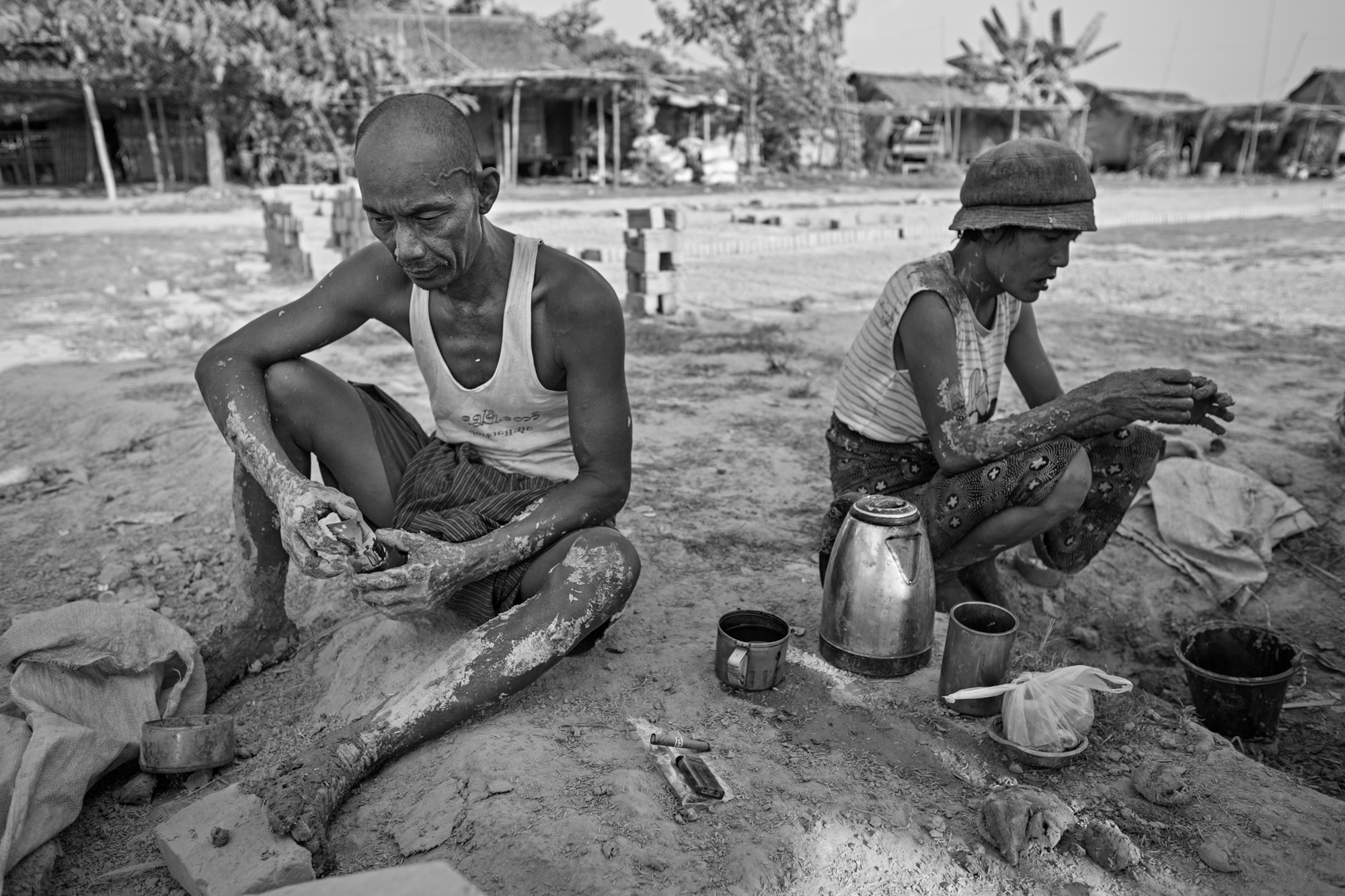 Naing Lin and Than Nwe rest during midday. They subsisted on very little, often eating only two sparse meals per day. For the most part they drank only a little tea, smoked cheroots (local cigars), or chewed betel nut (a natural stimulant), to get through the day.
