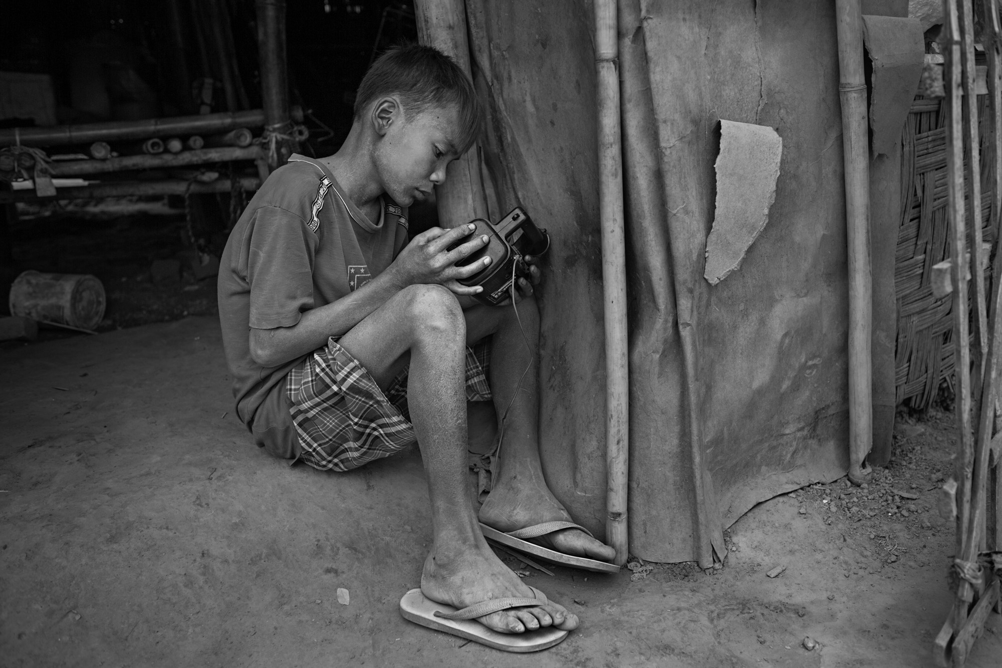 Naing Lin Oo leans against the door of his family's hut and tries to get reception on an old radio. He often became very angry about having to give his parents the money he earned, and treasured anything he could keep for himself.