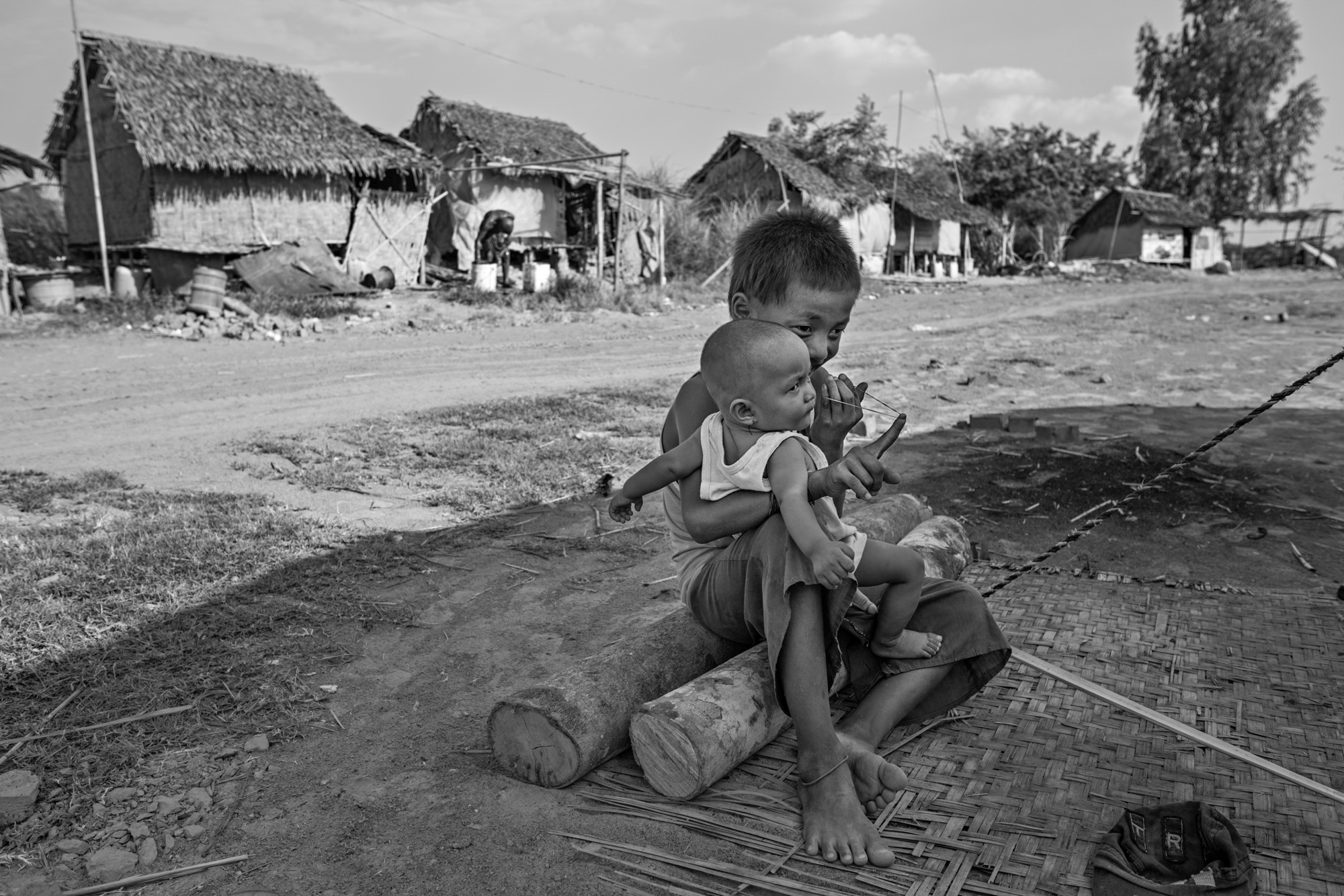 Than Ko holds his baby sister, Sandar Lin, while preparing to shoot a rubberband at his other sister, Saung Ning Wai. Than Ko is the primary caretaker of Sandar Lin during the day while his mother and older brother work.