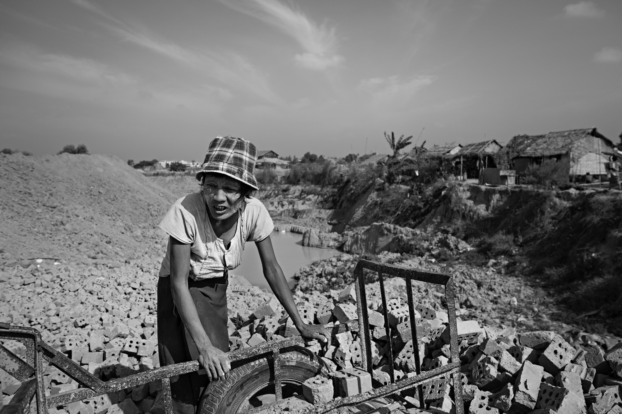 Than Nwe rests in the hot midday sun, leaning on a rusted cart she has been using to haul ruined bricks to a discard pile.