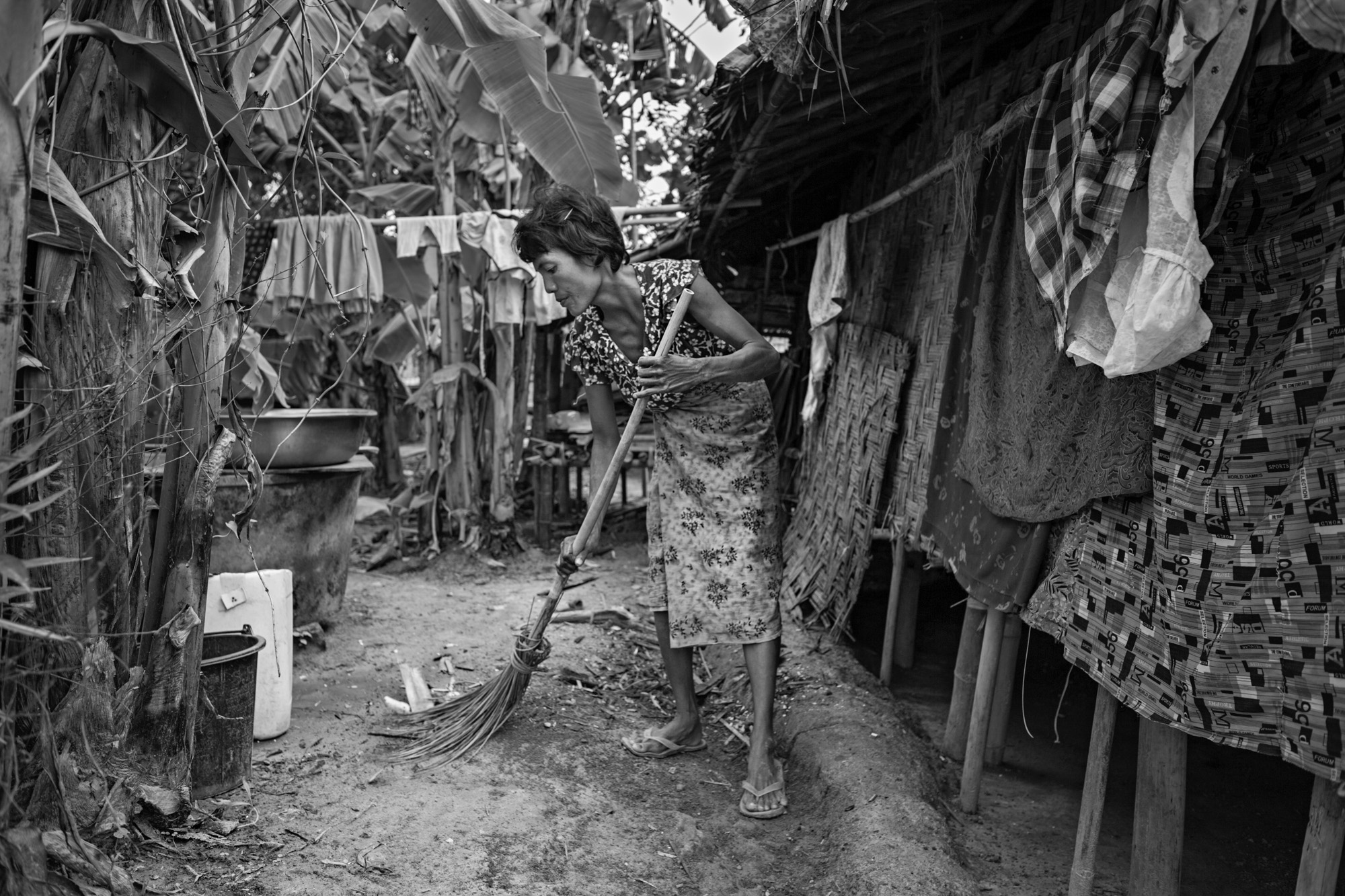 Than Nwe Sweeps up the area around her hut. In addition to earning money, she also cooks, keeps the house, gardens, cares for the children, and takes care of most of the discipline. After her husband died, the amount of work and responsibility increased.