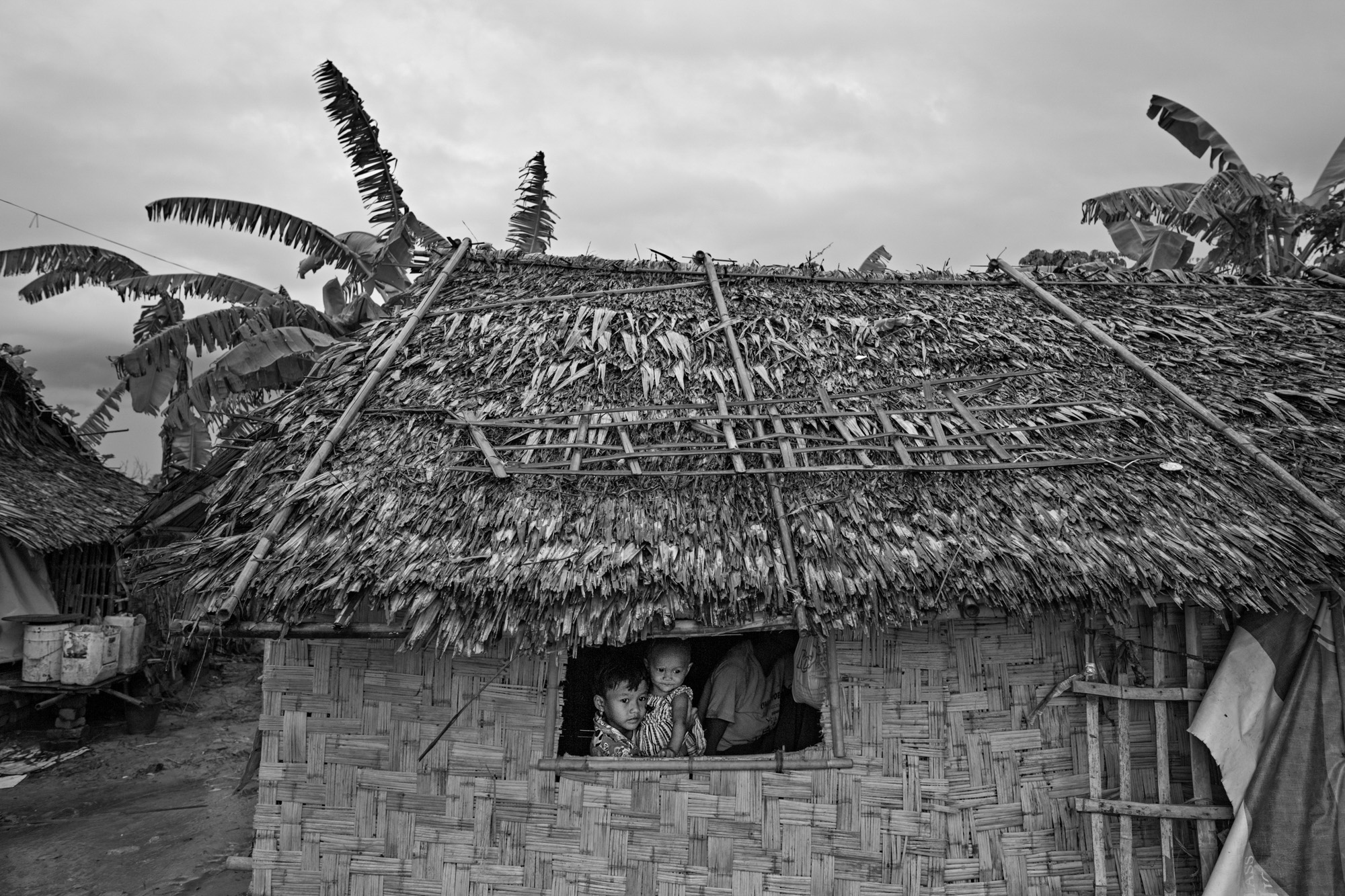 Saung Ning Wai holds her baby sister, Sandar Lin, as they gaze out of their hut on a rainy afternoon.