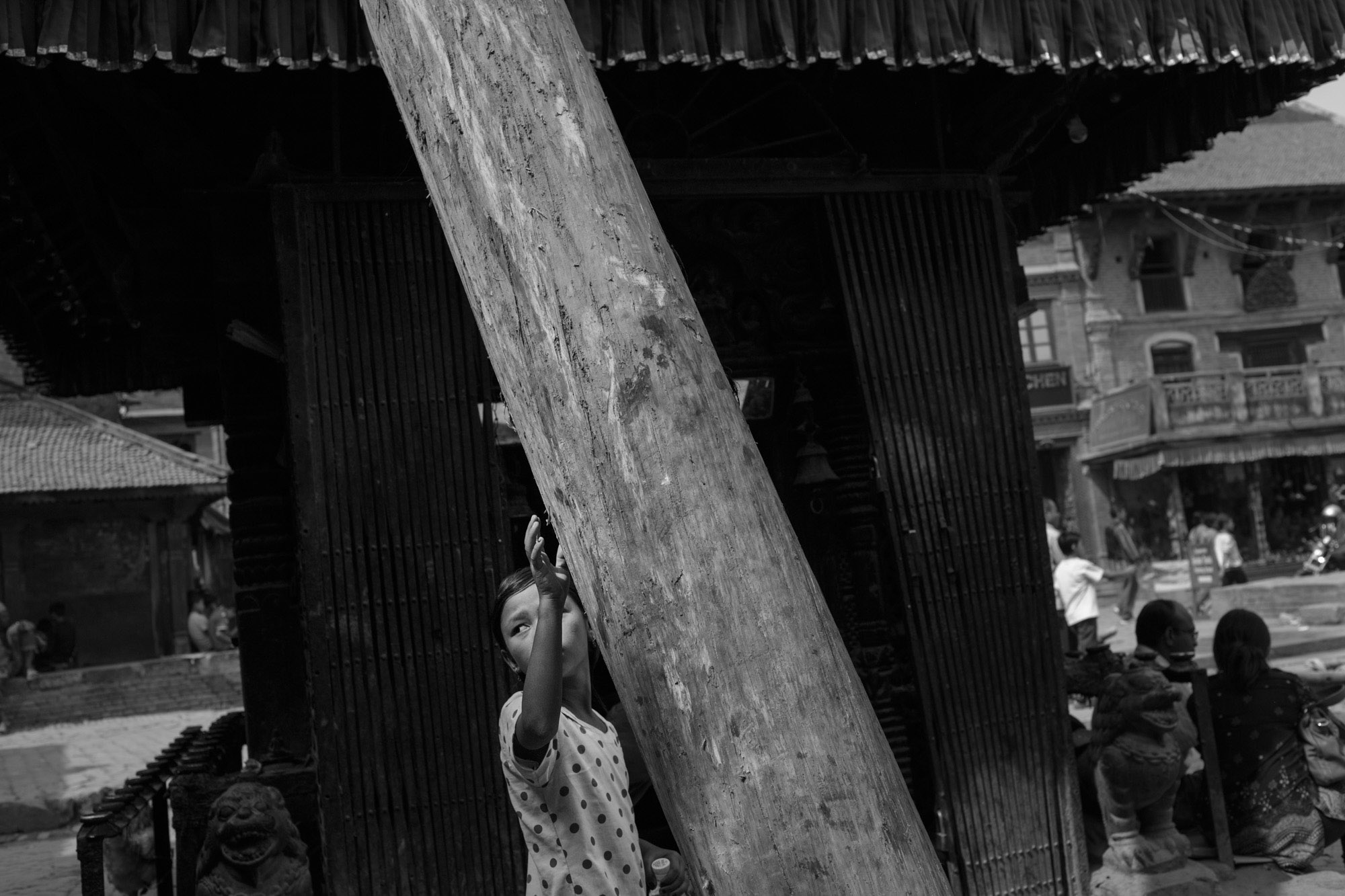 A young girl places her hand on a tall wooden pole believed to bring good luck during the Nepali New Year.