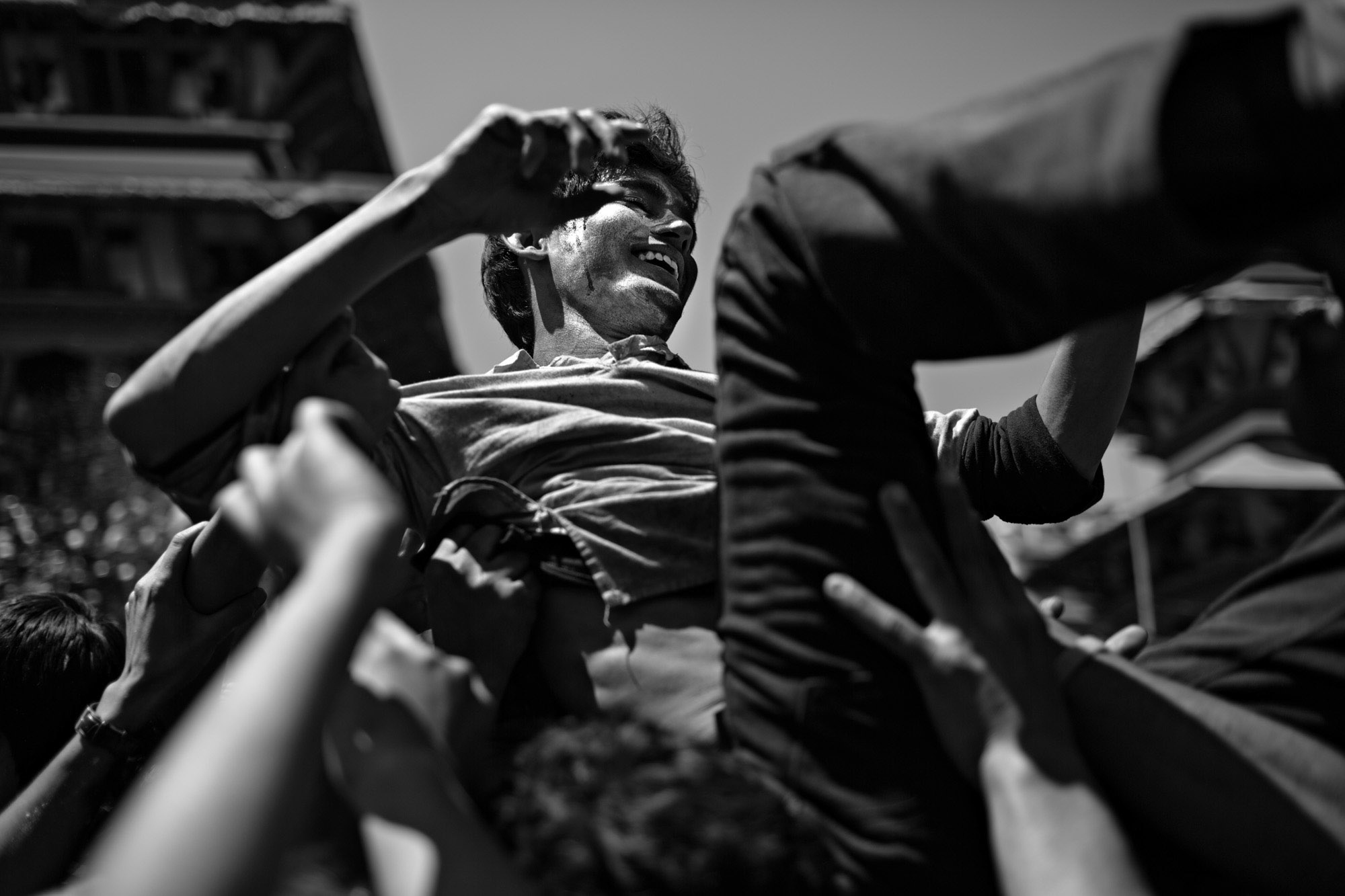 A young boy crowdsurfs during an outdoor party in Kathmandu's durbar square.