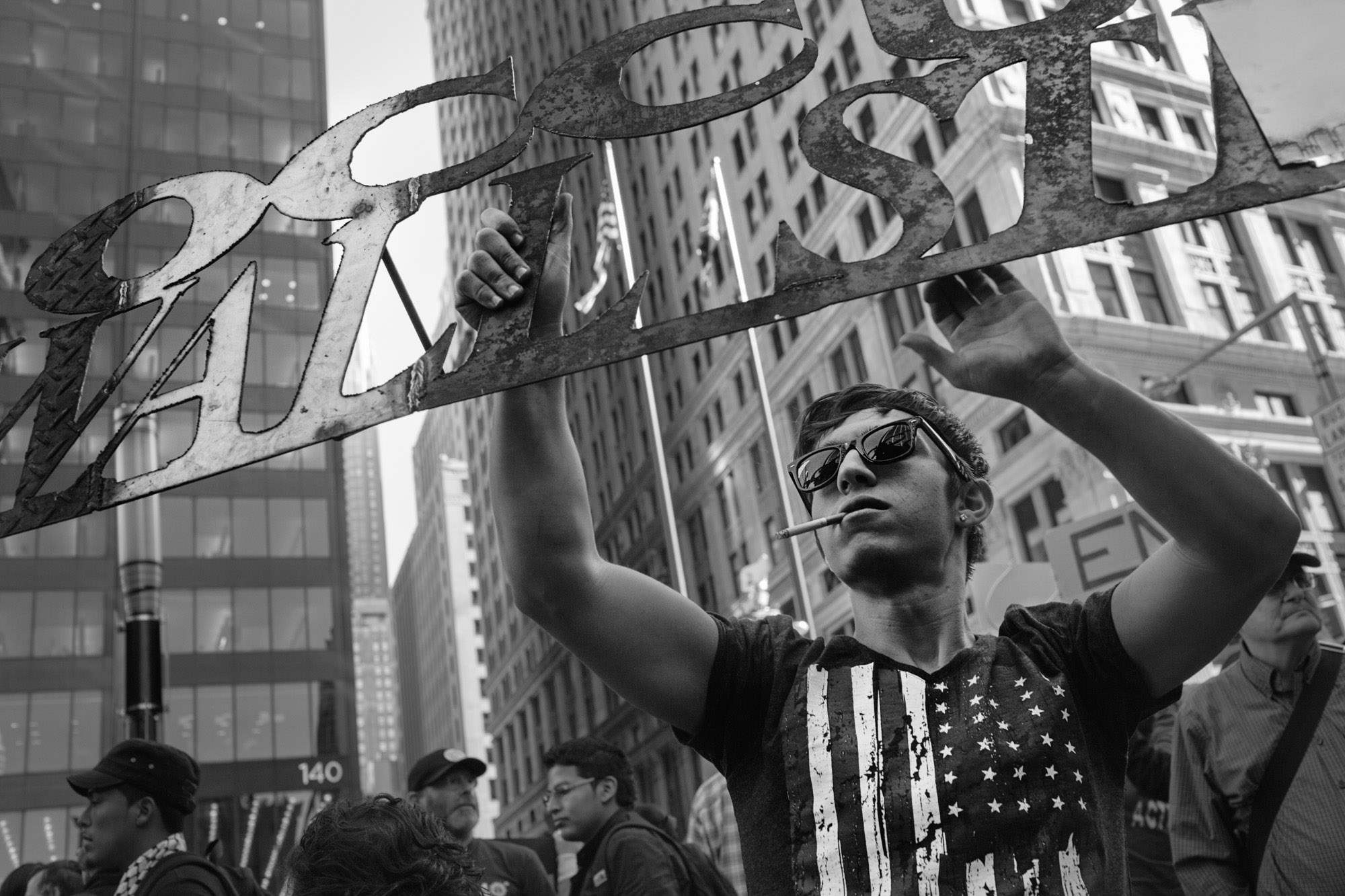 An OWS protestor holds an Occupy Wall Street sign cut from metal.
