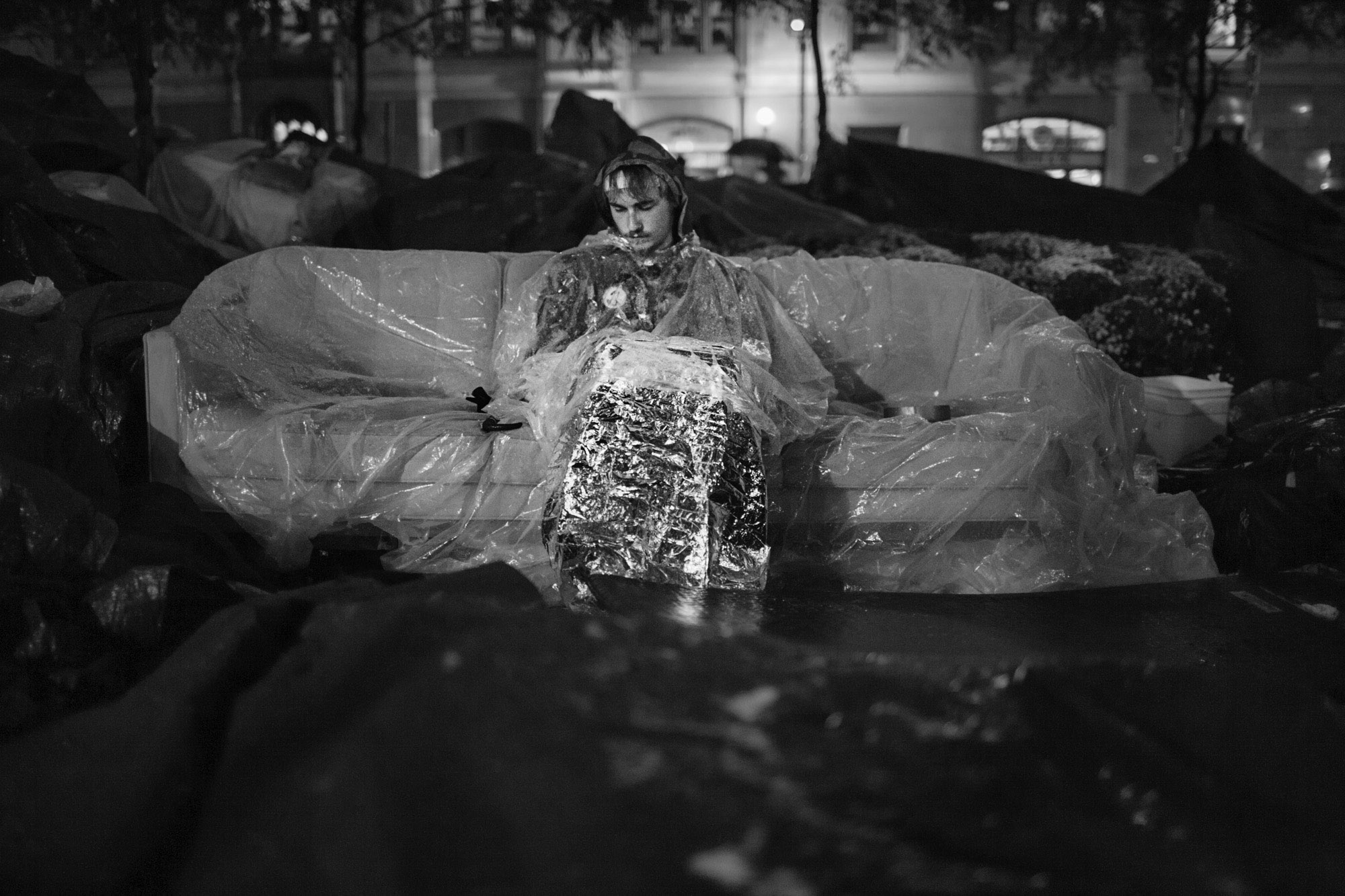 An OWS protestor sleeps sitting upright on a couch, in the rain, in Zuccotti Park.