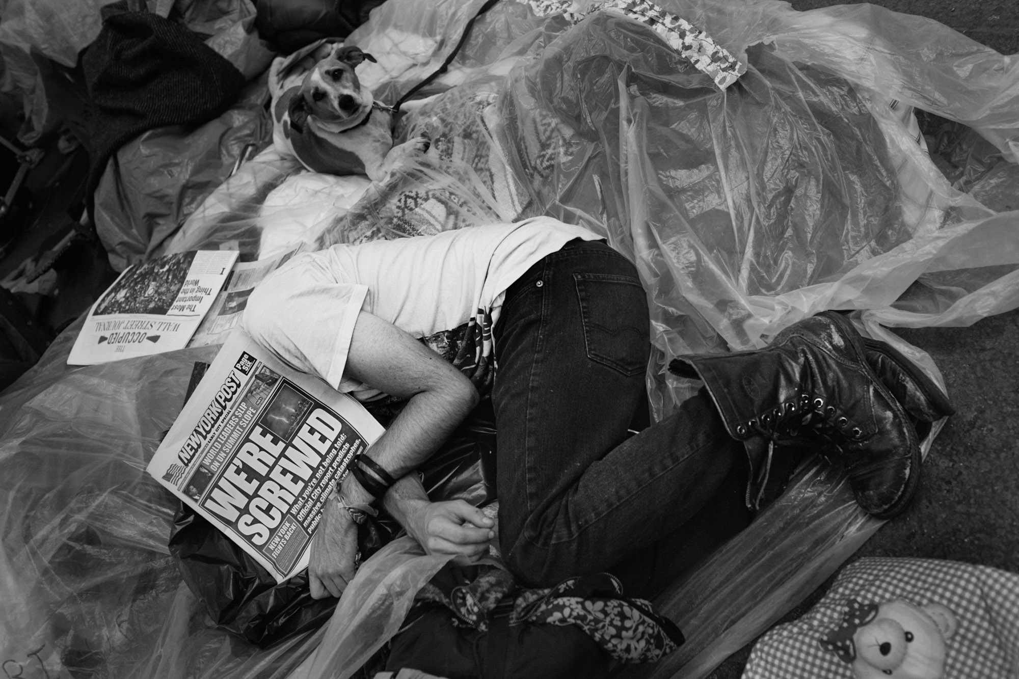 An OWS protestor sleeps with a newspaper over his face.