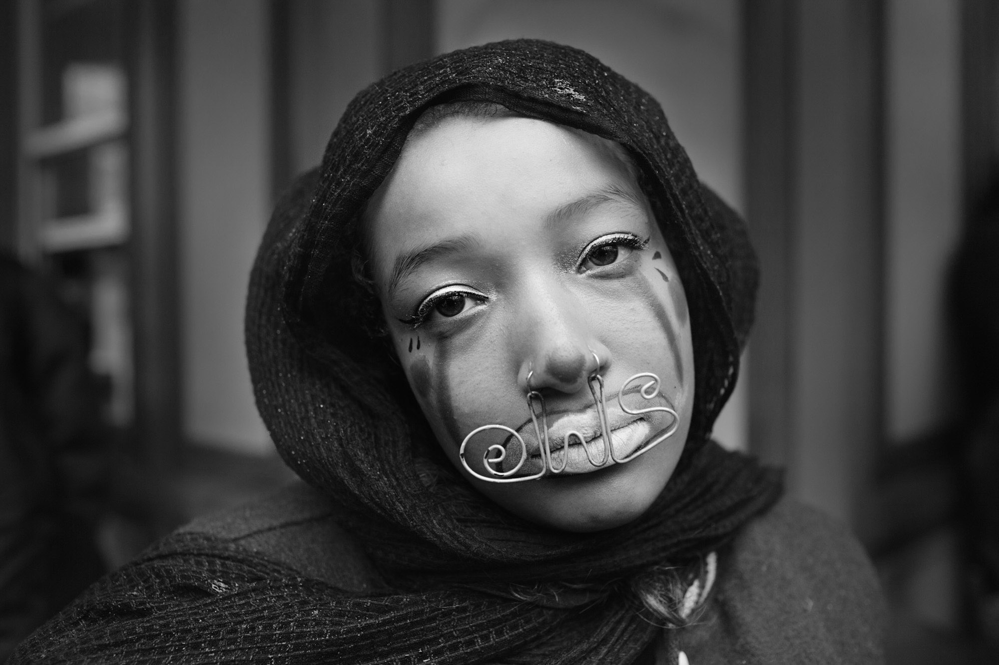 "A OWS protestor poses for a portrait, metal wire, hanging from her piercings, reads, ""OWS."""