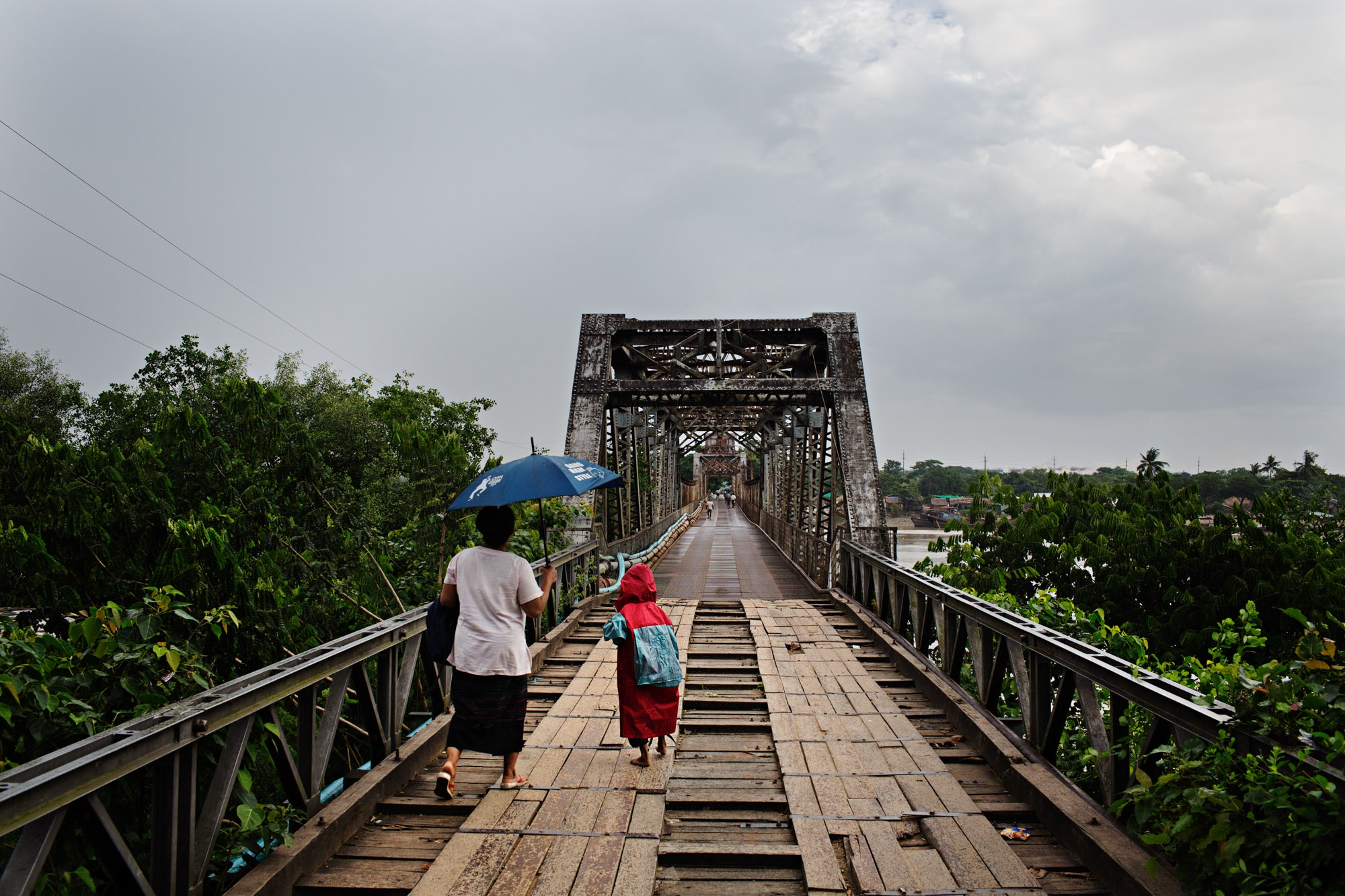 People walk across the bridge that leads to the gravel mining area.