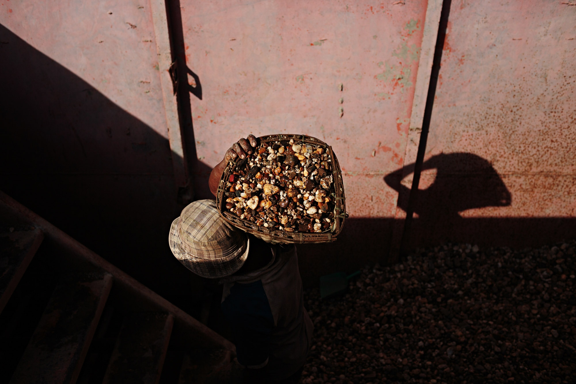A worker carries a basket of gravel up from the bottom of a dredging boat.