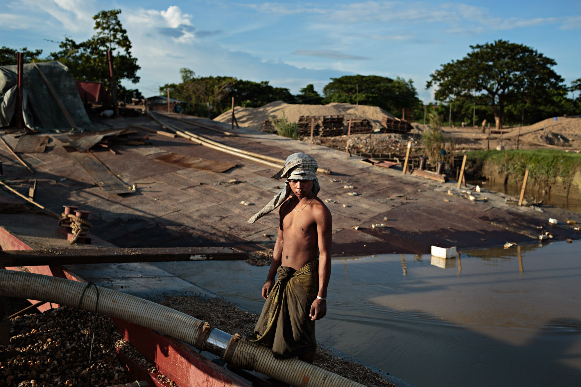 A young man pauses for a moment while working on a dredging boat.