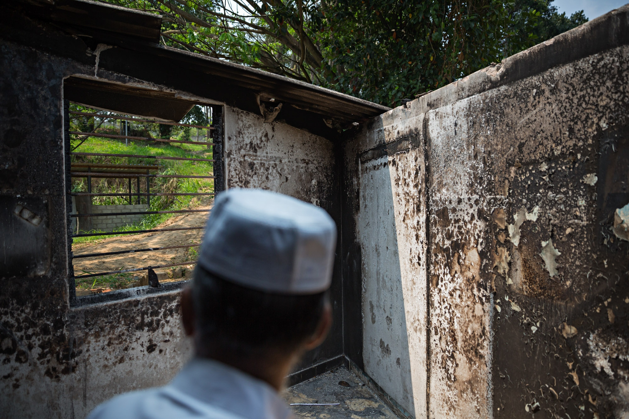 A man looks out of a burned out window at Masjidul Lafir Jummah Mosque in Digana, Sri Lanka.
