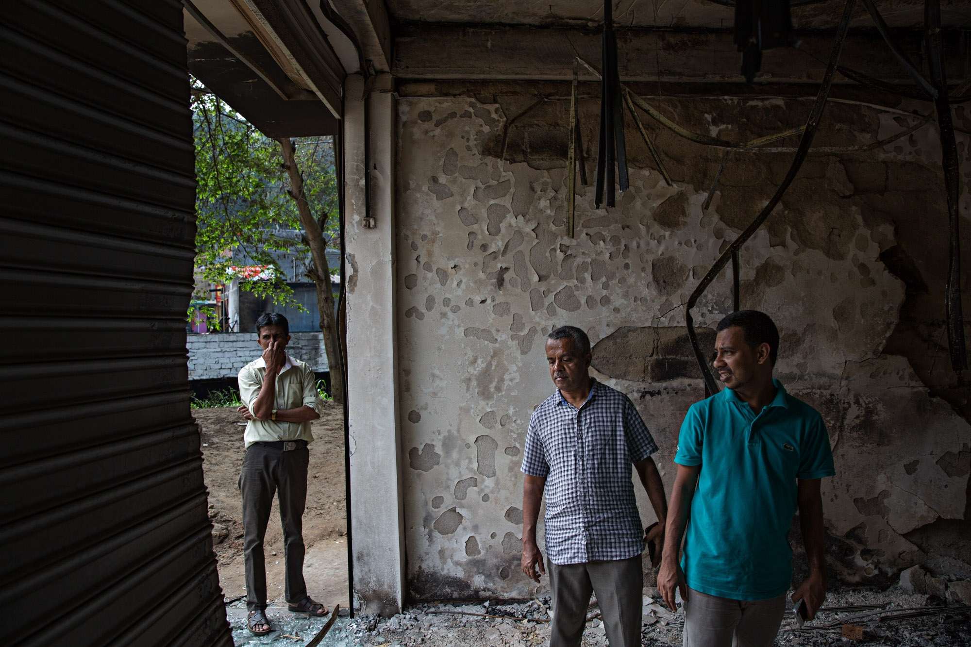 Zainab Hilmy's father (center) stands in the wreckage of his family's furniture store at Eighth Mile Post, Akurana, Sri Lanka.