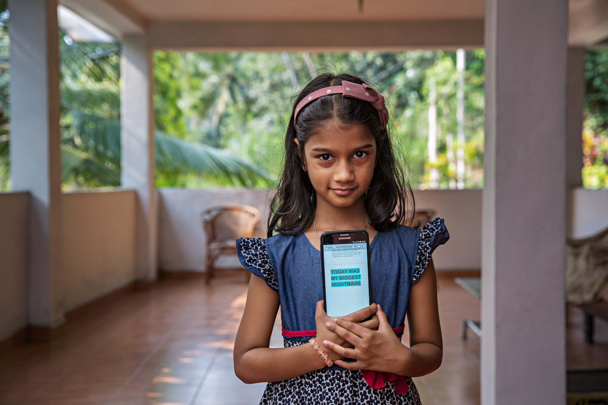 Zainab Hilmy's niece, Aaliyah Dilshan, holds a digital copy of her account of the night the furniture store was destroyed, at her home at Eighth Mile Post, Akurana, Sri Lanka.