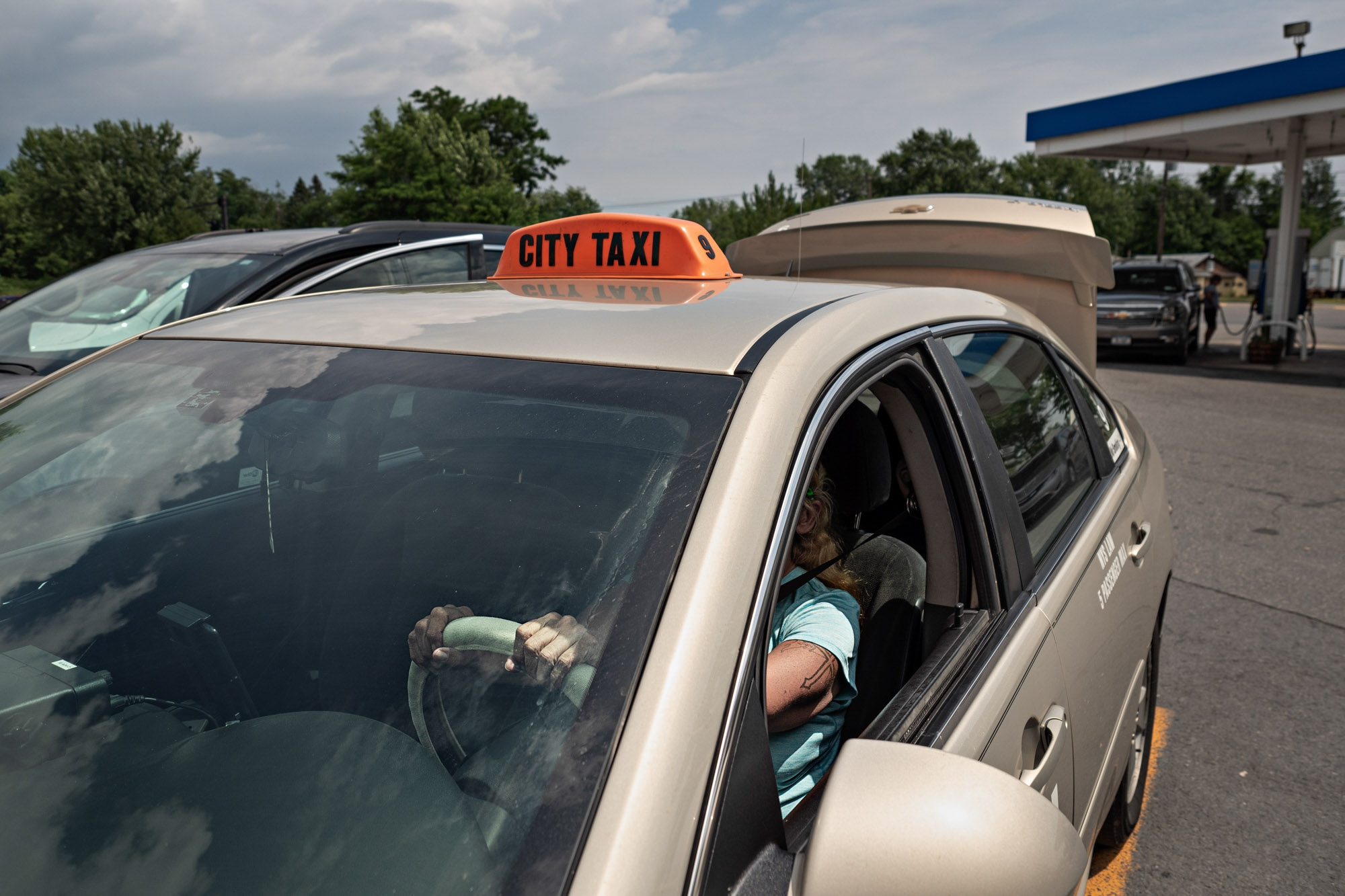 A taxi driver (who preferred not to have her face or name shown) sits in her car for a photo. She regularly carries people from this Mobile station to the boarder crossing on Roxham Road.