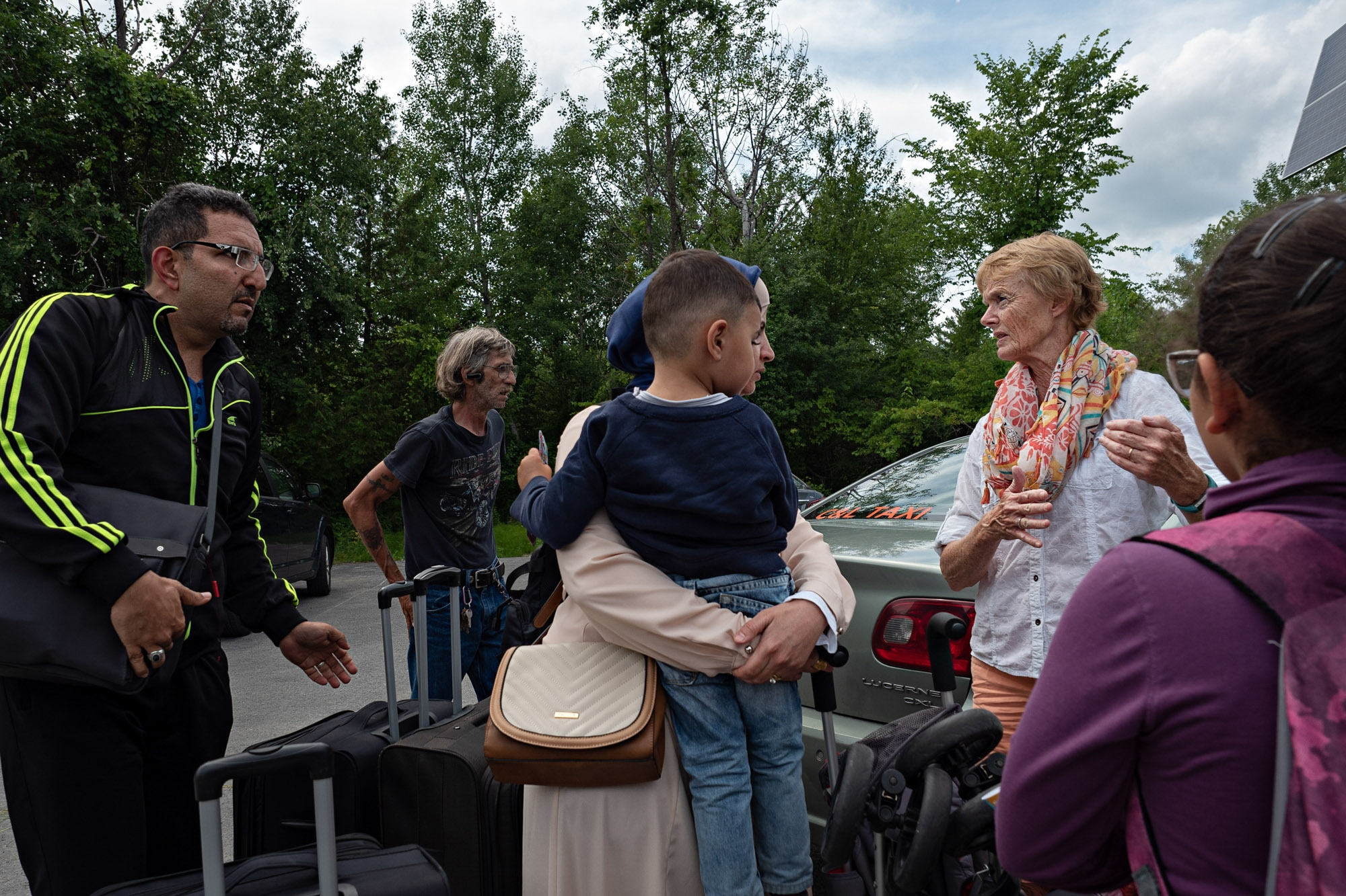 Janet McFetridge, 66, explains to a family of Palestinian asylum seekers what will happen when they try to cross the border. McFetridge waits at this waypoint year-round, offering snacks, clothes and toys for children on the journey to Canada.