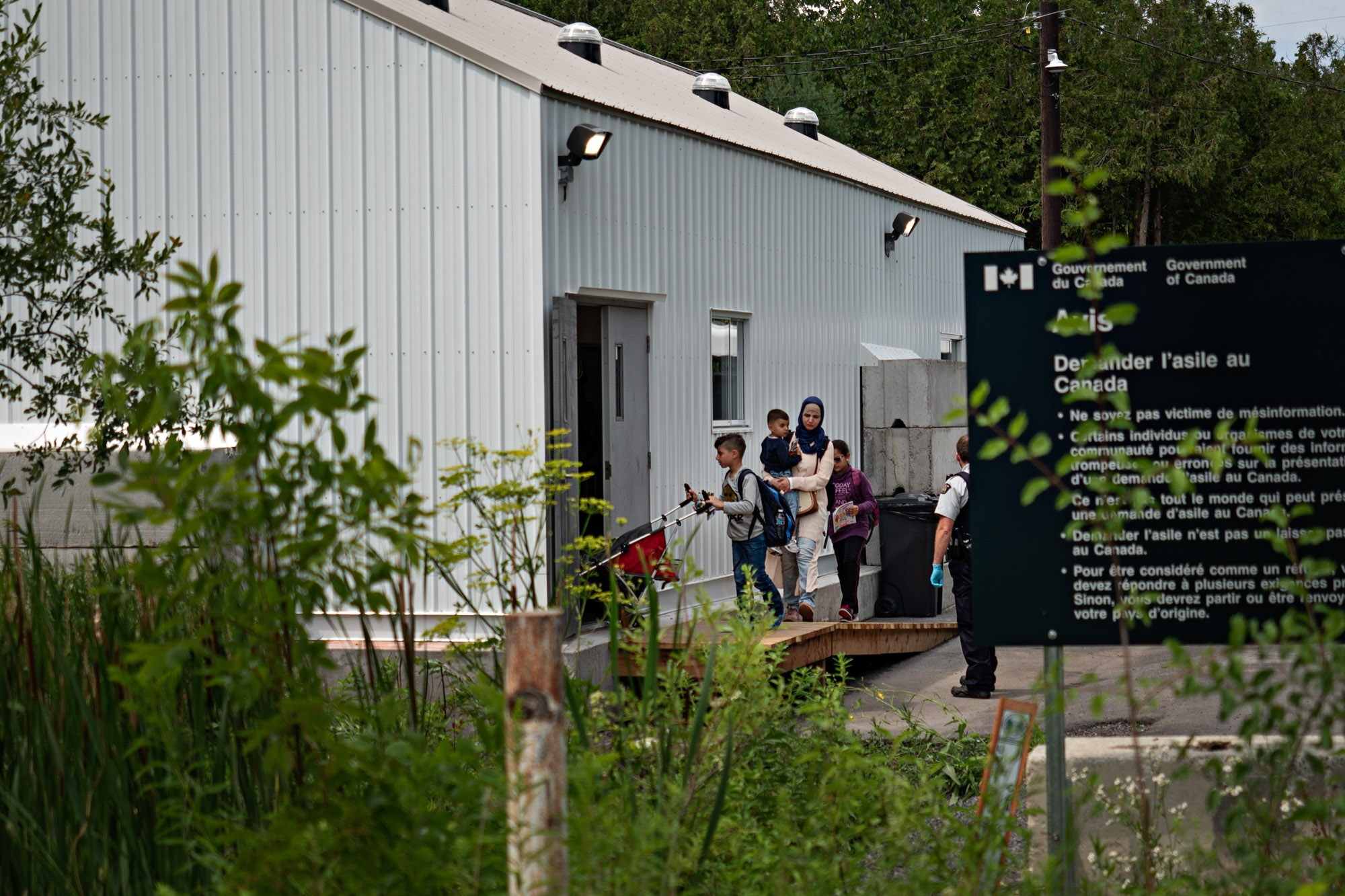 Asylum seekers enter a shelter on the Canadian side of Roxham Road, which starts near Champlain, N.Y. The outpost was built to help process the recent surge of refugees and asylum seekers, which can total about 50 people a day.
