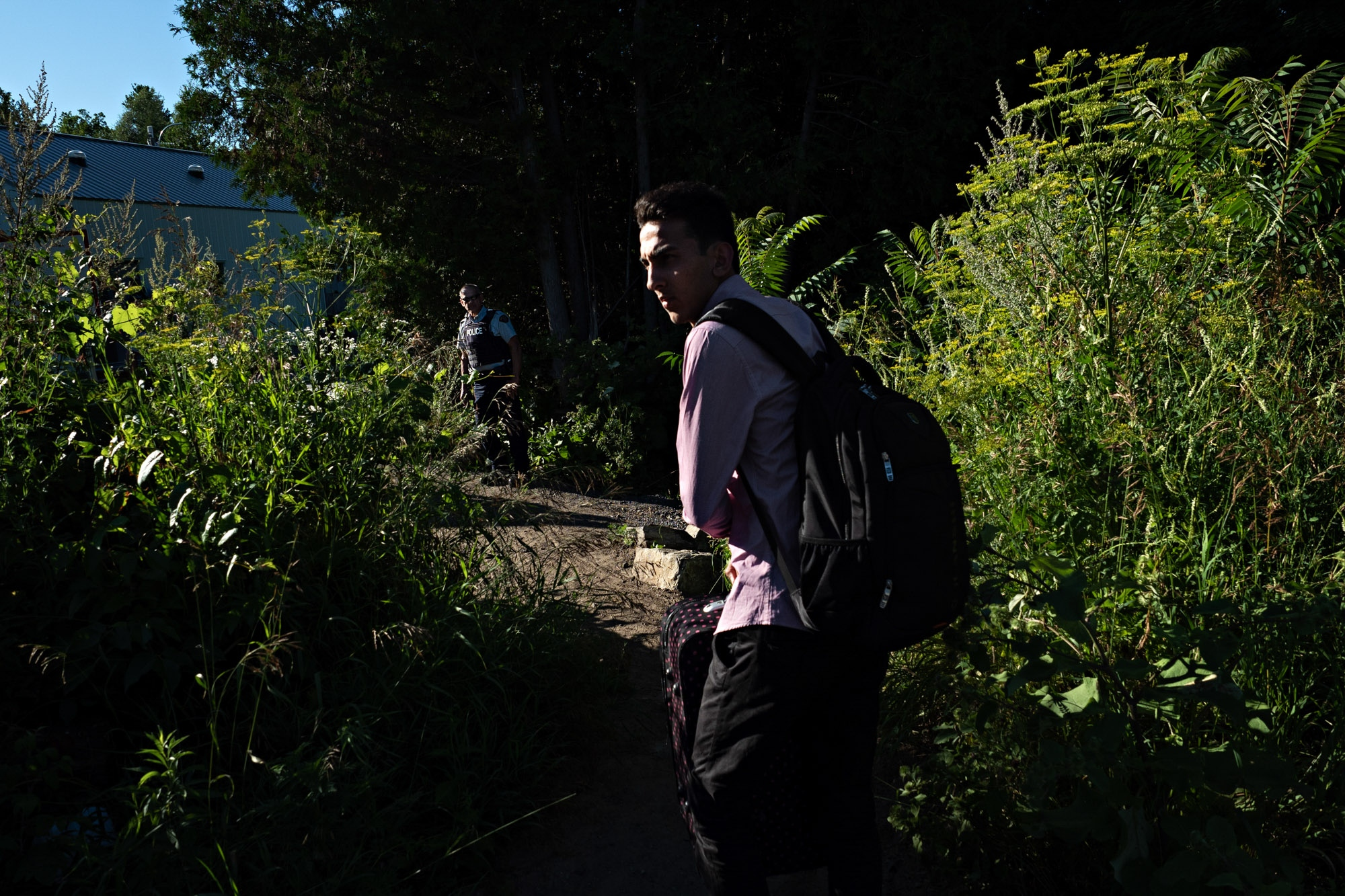 Omer Malik, 19, takes a last look back toward the United States before crossing illegally into Canada at the end of Roxham Road in Champlain, N.Y.