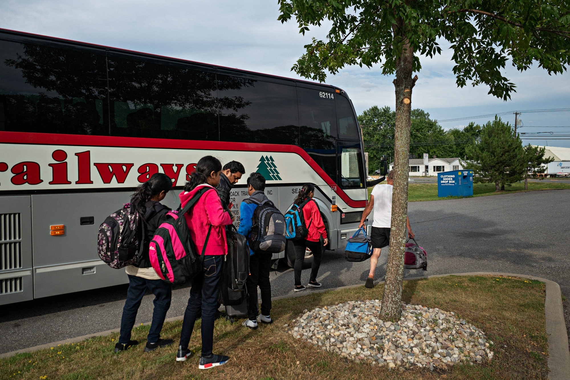 A family gets of a bus as they prepare to head to the Canadian boarder.