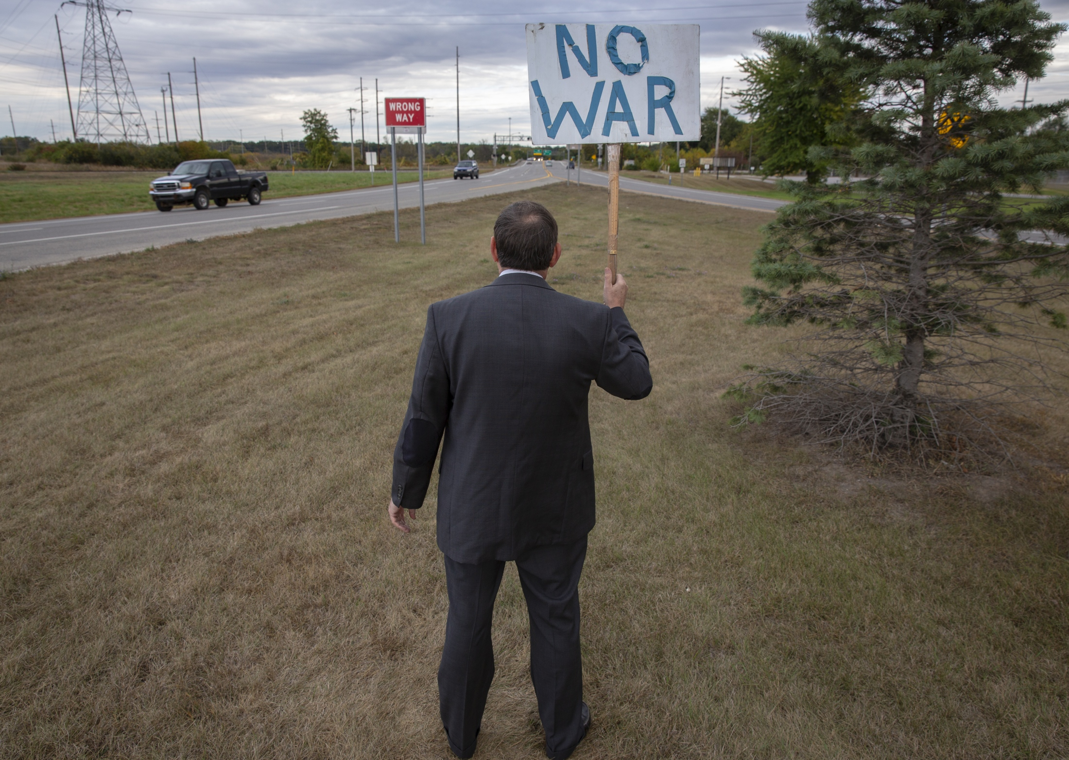 "Steve Beck stands holding an anti-war sign on the way back from work at the Veterans Memorial Causeway in Muskegon, Mich. on Oct 5, 2017. Working daytime as a title officer, Beck originally protested since 2006 against the U.S. invasion to the Middle East every other day after work until Obama took the office. ""And then Trump came in. And in the first few months, he goes to the United Nations and threatened other countries. So I said, 'well, I'll go back again,'"" Beck said. ""I'm just standing here for peace. People are honking, so they're thinking about it."""