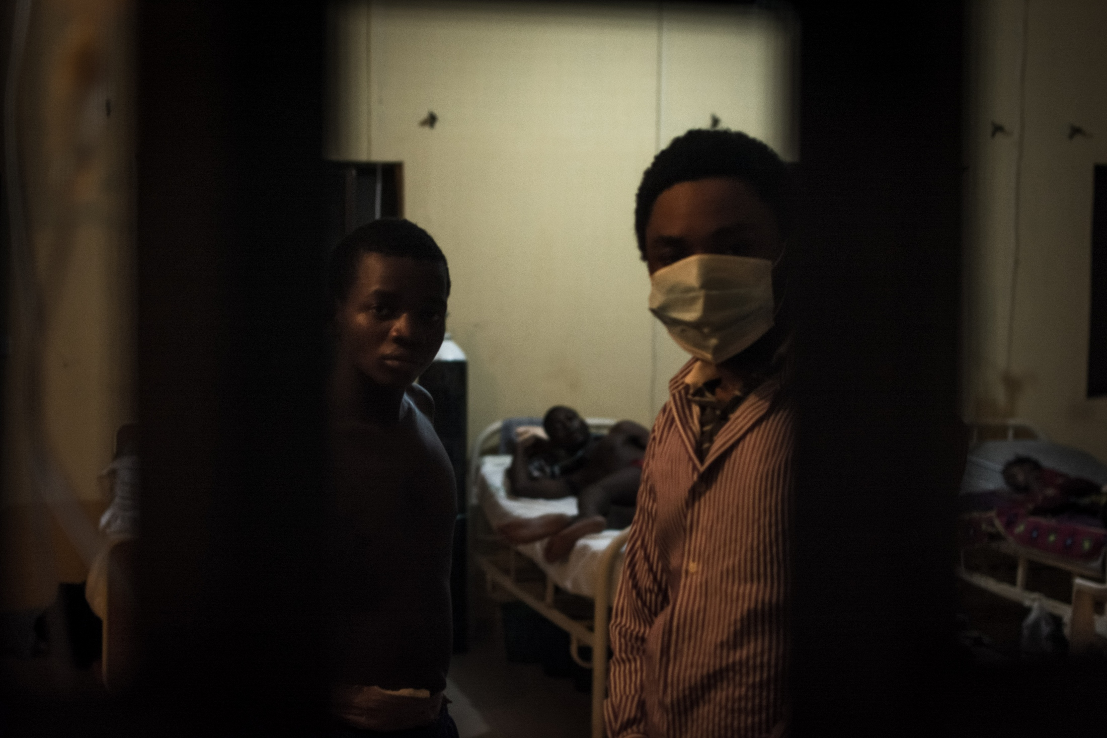 Just before they go to bed, two young men look out of the window at the male ward for Lassa patients at the Irrua Specialist teaching hospital in Edo State.