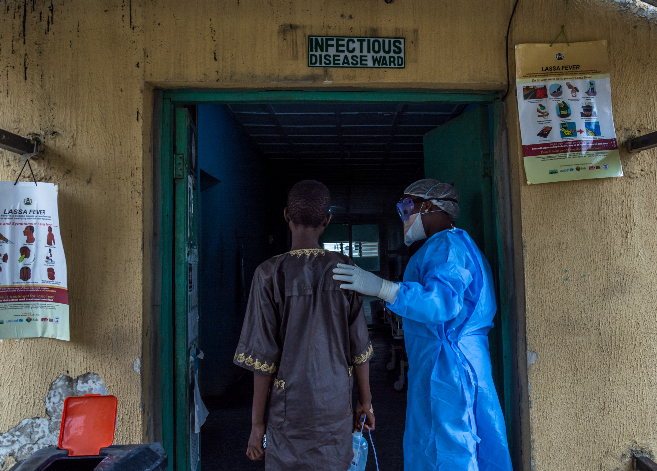 A nurse accompanies a patient suspected to have Lassa fever to the isolation ward at the Federal Medical Center, Owo, Ondo state.