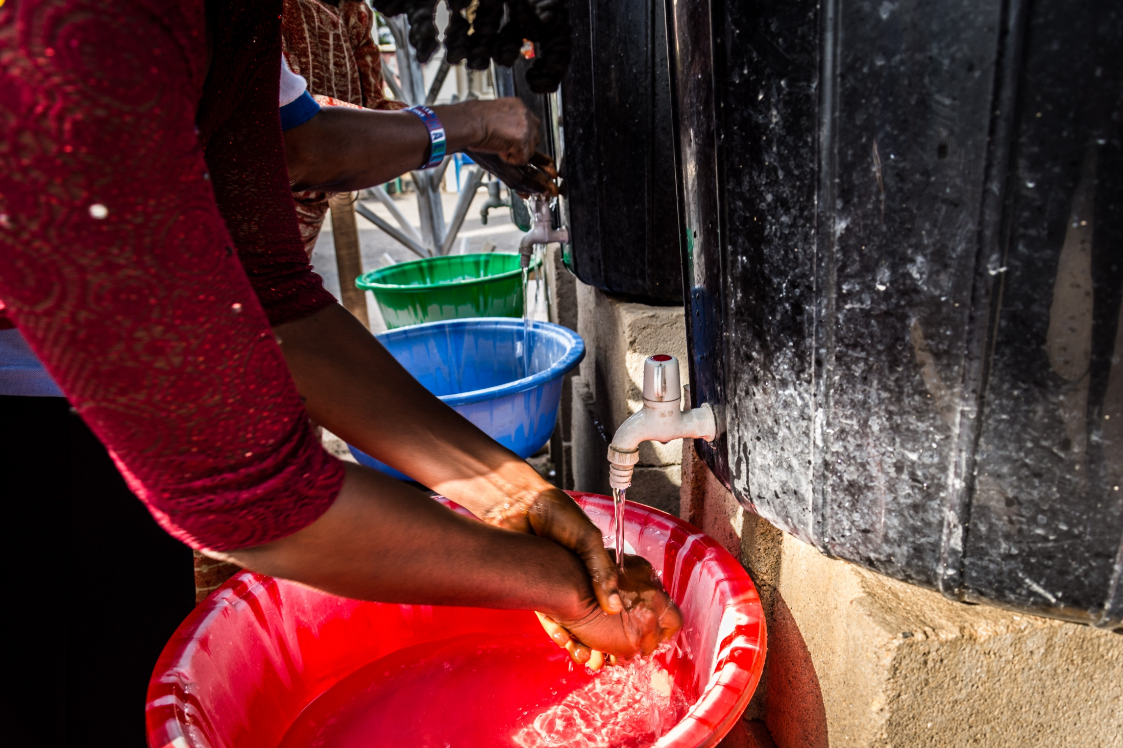 A middle-aged woman disinfects her hand with chlorinated water upon entering the Federal Medical Center, Owo, Ondo state. ALIMA donated portable water storage facilities which are placed in different parts of the hospital. They usually contain 0.05% of chlorinated water.