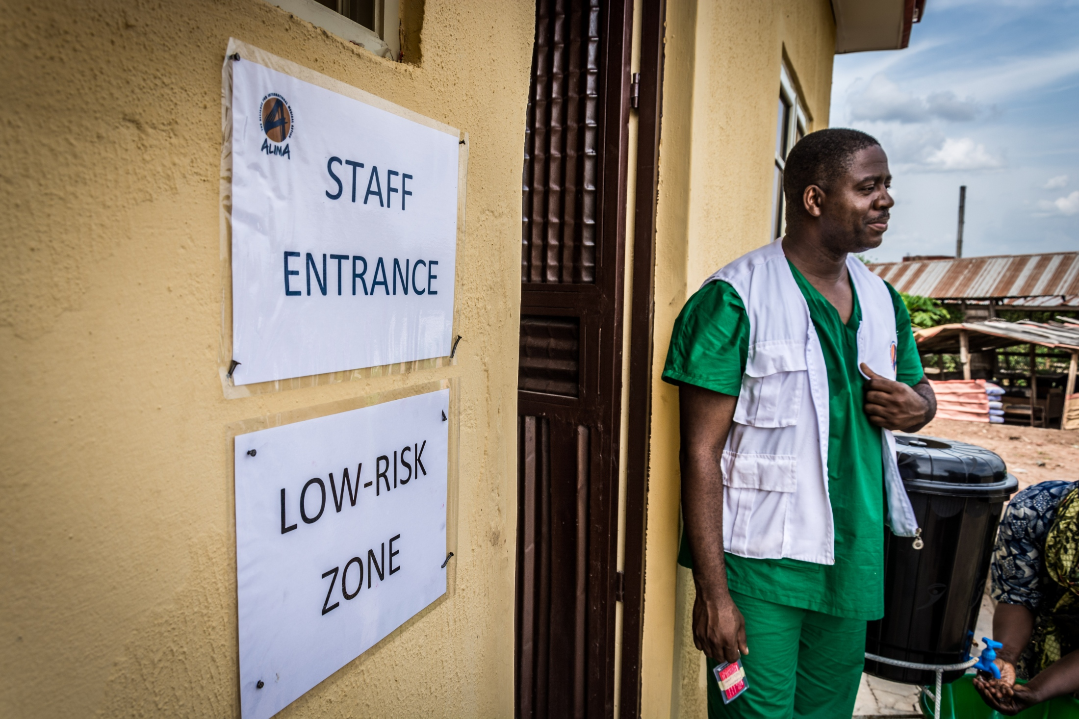 Dr. Dally stands in front of the Staff Entrance at the Infection Control Centre (ICC) iat the Federal Medical Centre, Owo, Ondo state. The Staff entrance, is considered a low risk zone because patients don't have access to the area.