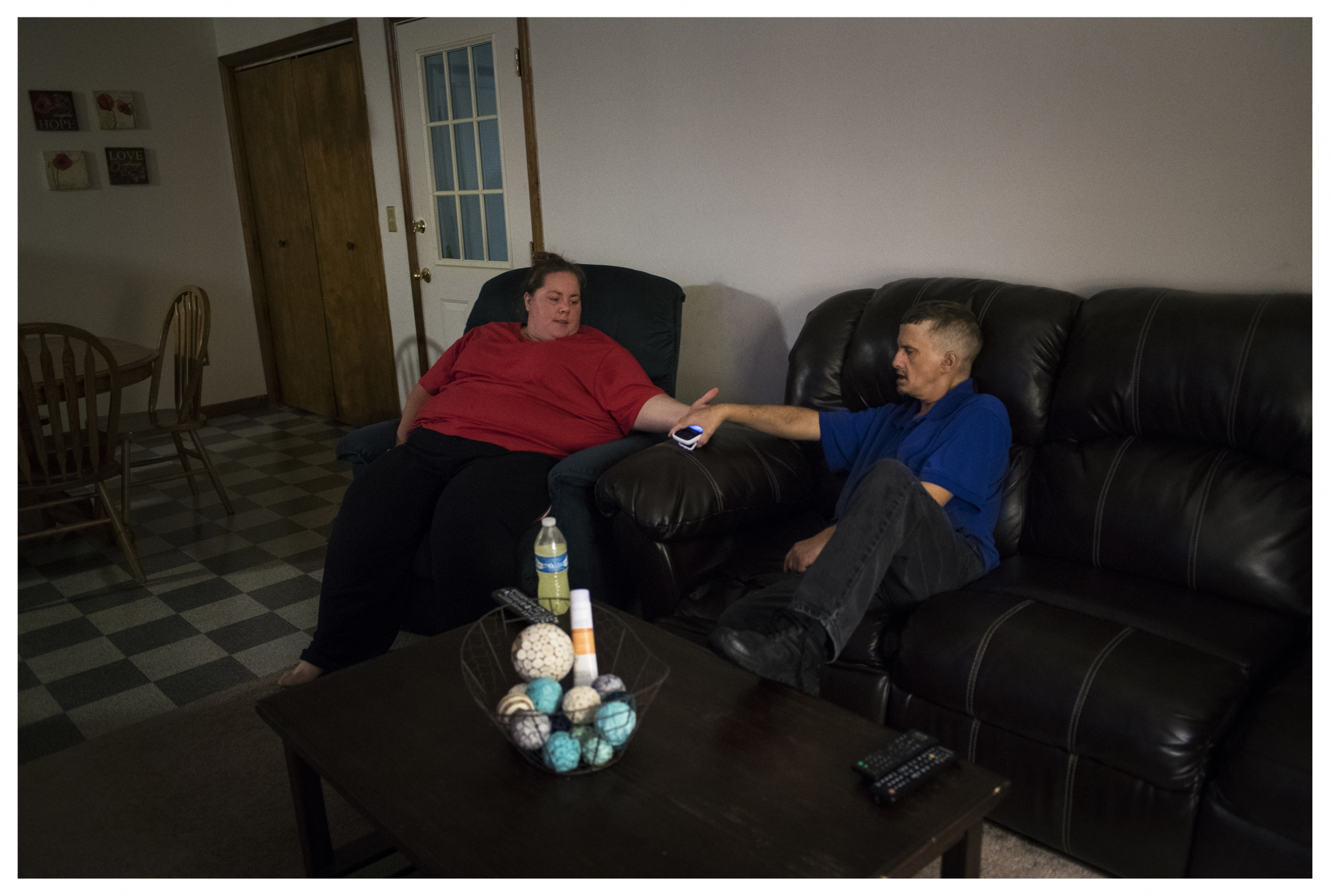 Natalie Weaver, a House Manager from D&S Community Services, holds Tony's hand after his work shift. Natalie is one of three managers who rotate residence in the home to support Tony and his roommate.