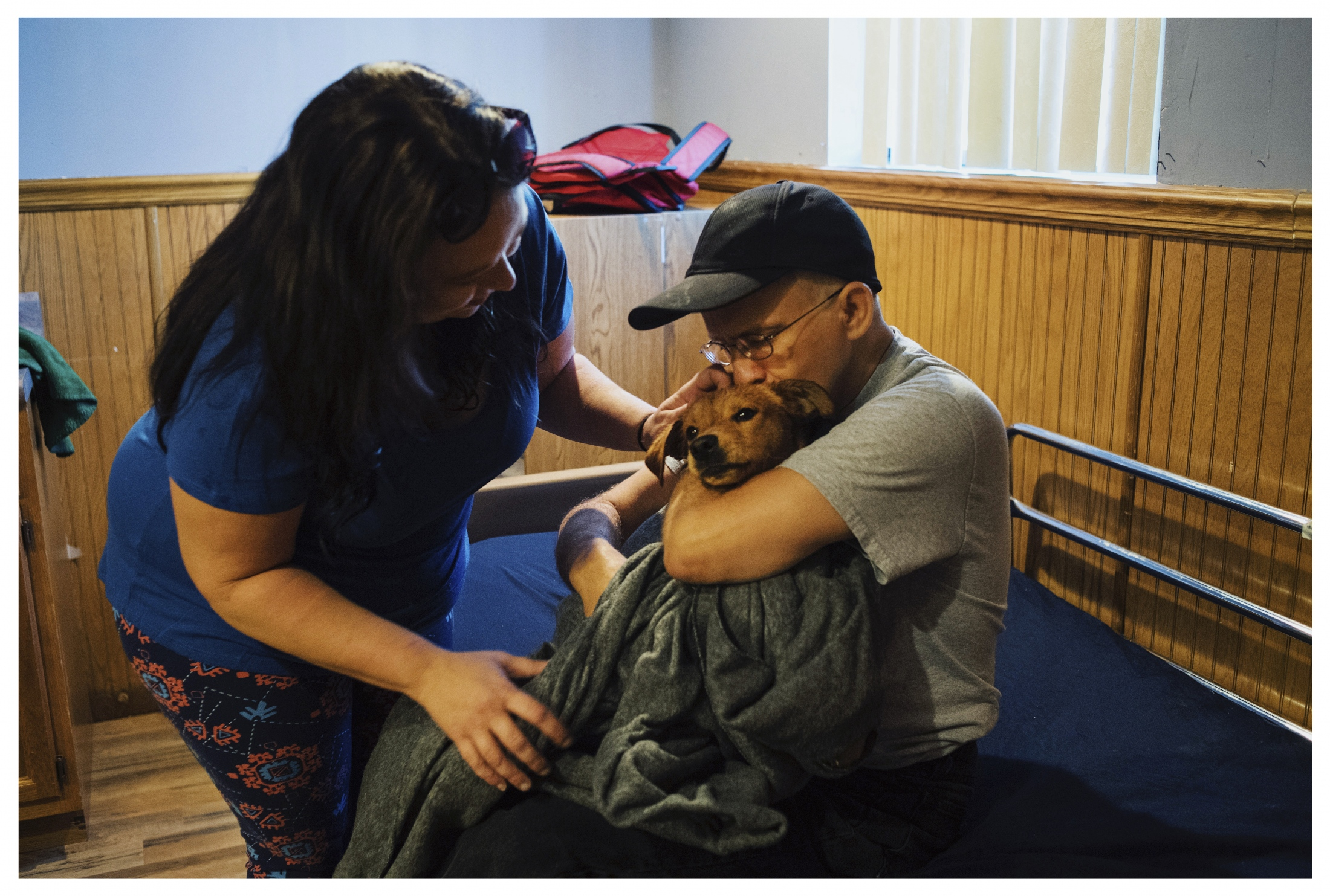 Tony embraces his service dog Bertram before he is sent off to Buffalo, New York for training. The two won't see each other again until Christmas. Service animals such as Bertram help individuals with disability gain independence.