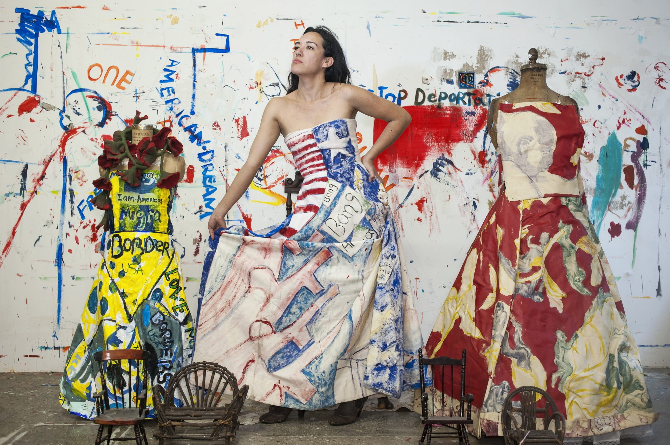 "Maria De Los Angeles is a Mexican American painter recognized for her painted dresses, which are wearable portraits of human displacement and the immigrant experience. Educated at Pratt and Yale, she is an undocumented immigrant smuggled across the border to California when she was eleven. She could not vote in this election due to her DACA status but said she would have voted for Bernie Sanders. She got her DACA status renewed for two more years in July. She has been making dresses since around February 2016, the beginning of the election campaign, interested in the confrontational aspect of wearing stereotypes on one's body. She uses acrylics, painting abstract scenes of migration to look like landscapes, or at other times writing overt commentary on deportation. ""I wanted to create a more nuanced portrait of immigrants,"" she said. ""And also place myself in my work."""