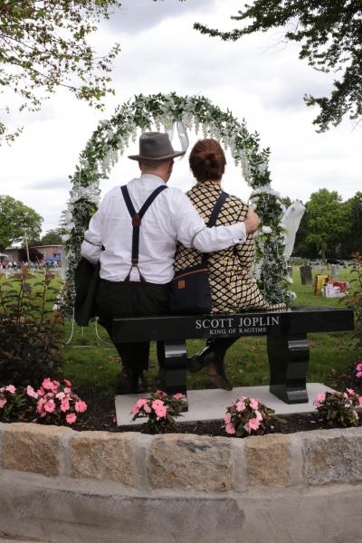 Couple posing for pictures on new bench at Scott Joplin gravesite, St. Michael's Cemetery. Astoria, June 2017