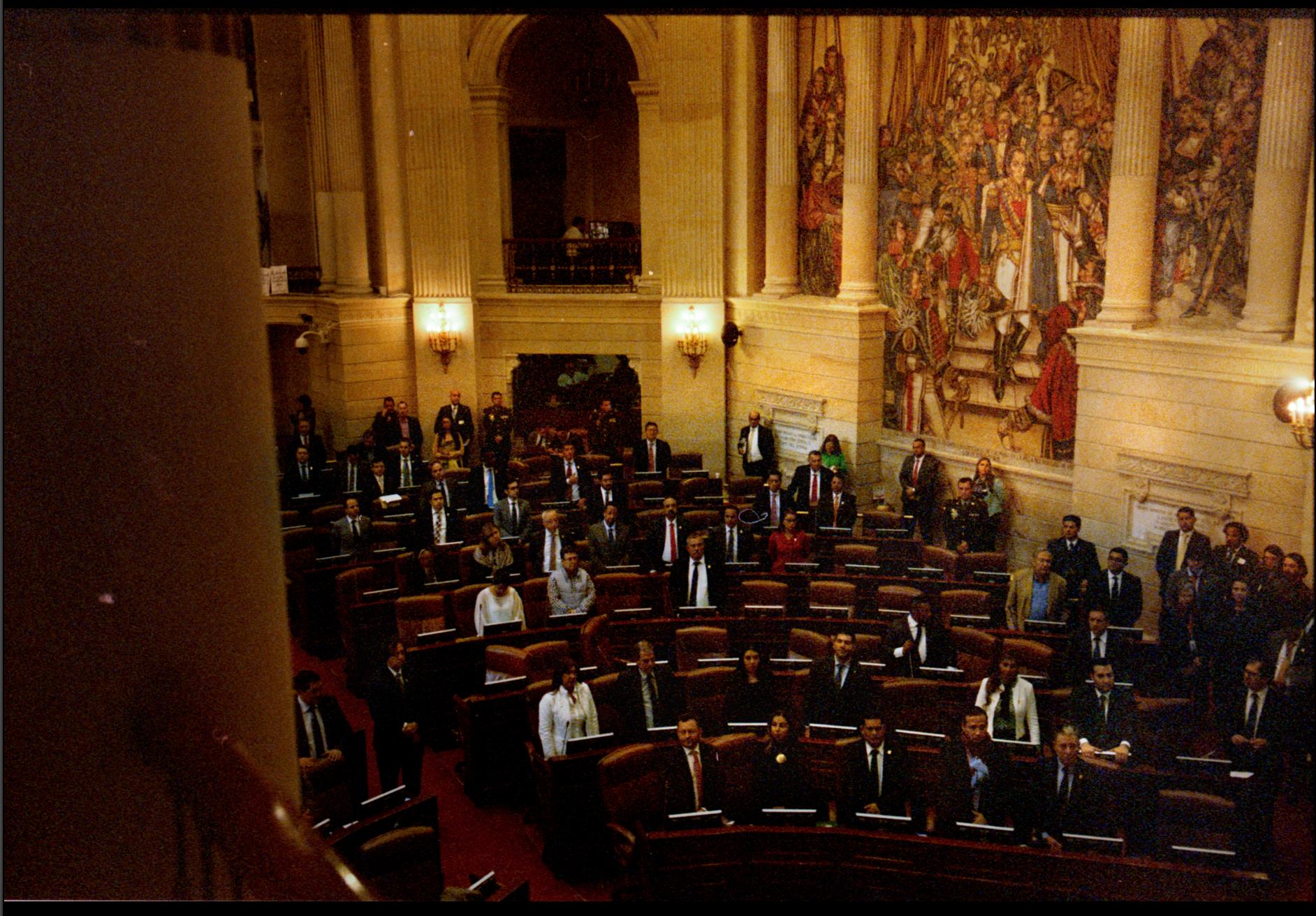 Miembros del Congreso de la República se mantiene de pie y en relativo silencio durante un minuto de silencio por el asesinato de líderes sociales.
